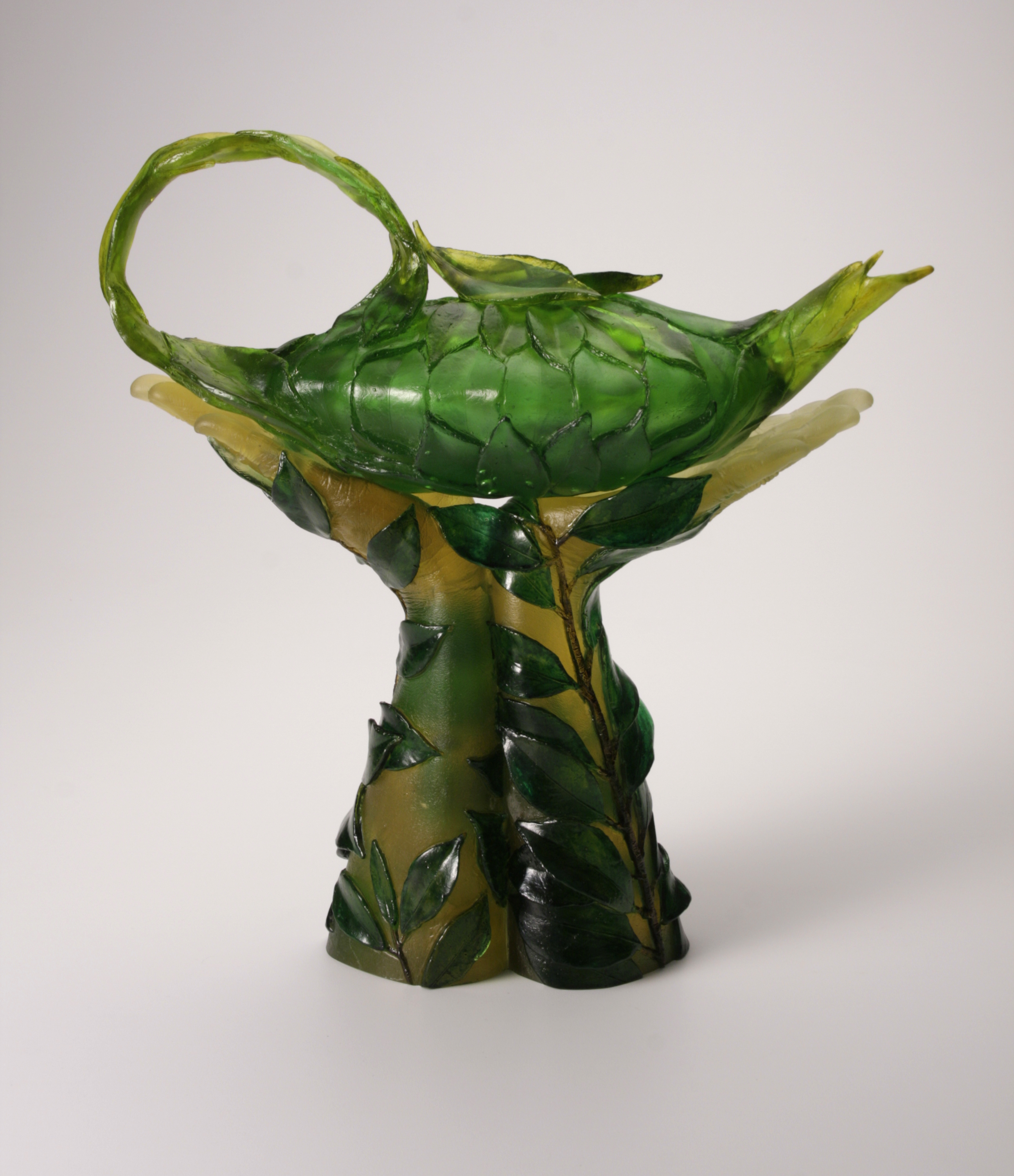 Sculpture of arms with tea vines wrapping them, holding a teapot made of leaves.