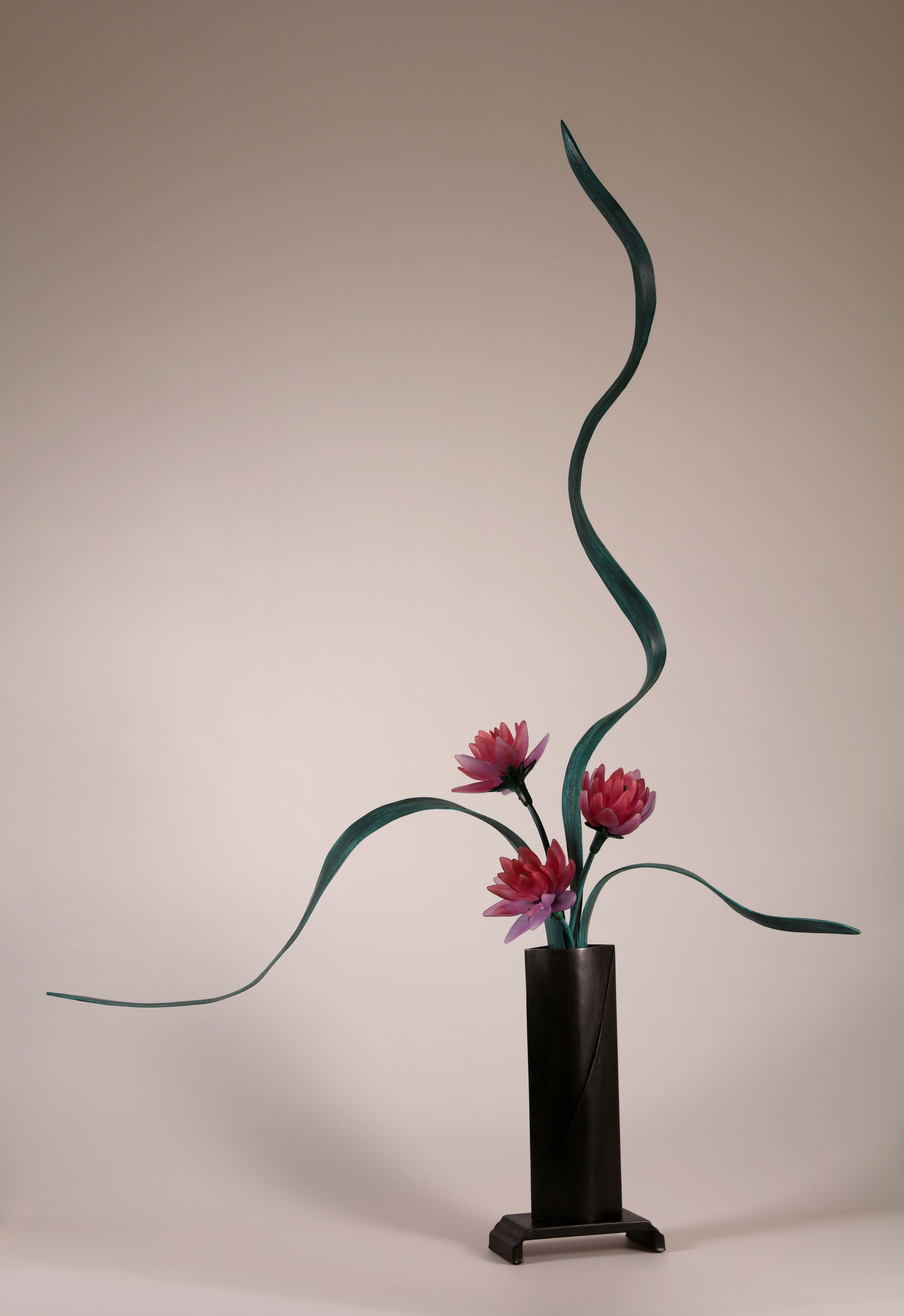 Sculptural flower arrangement in cast glass with ruby pink flowers, green steel leaves, tall vase in deep brown.