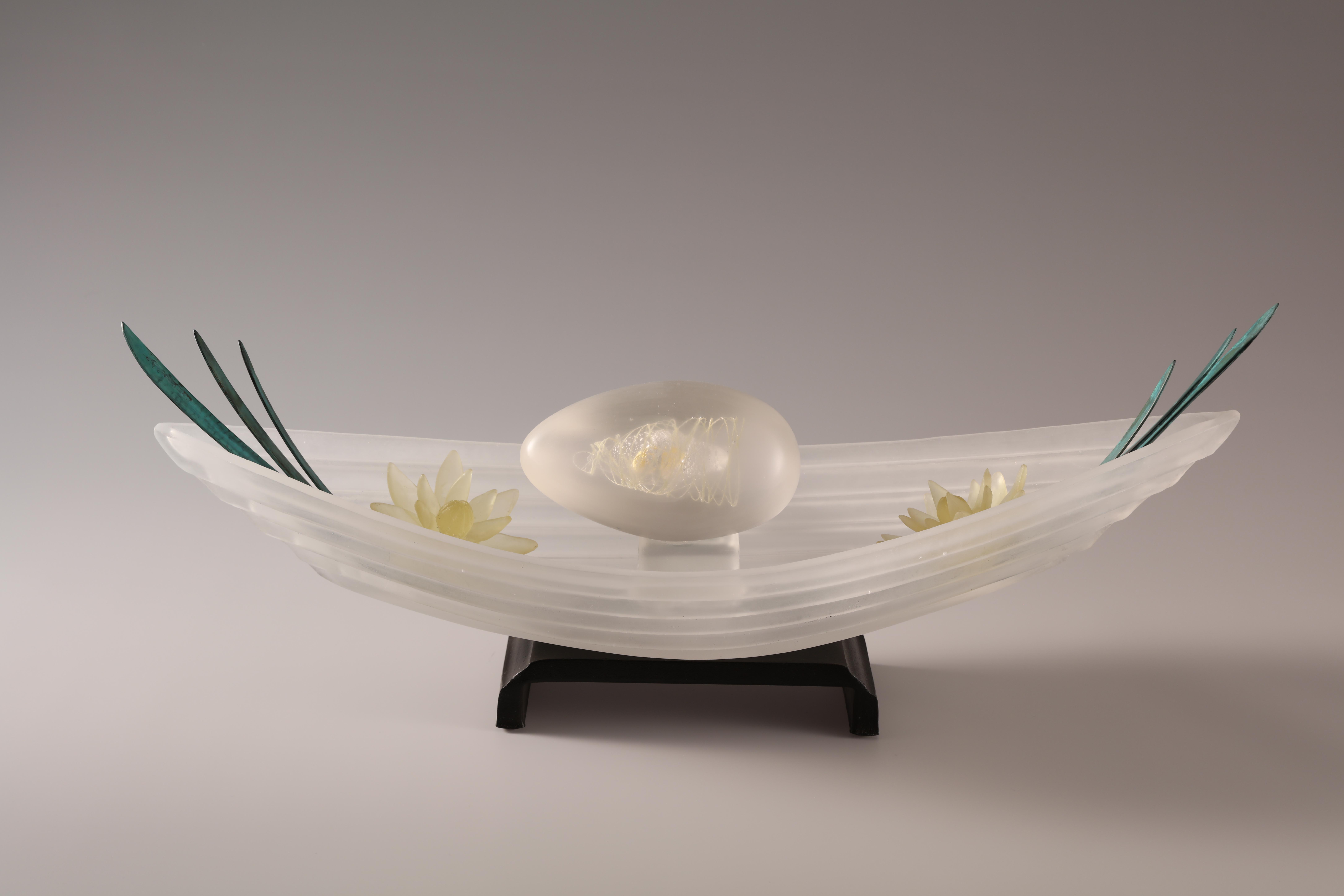 Sculpture of cast glass boat and amber flowers with bronze leaves on steel base.
