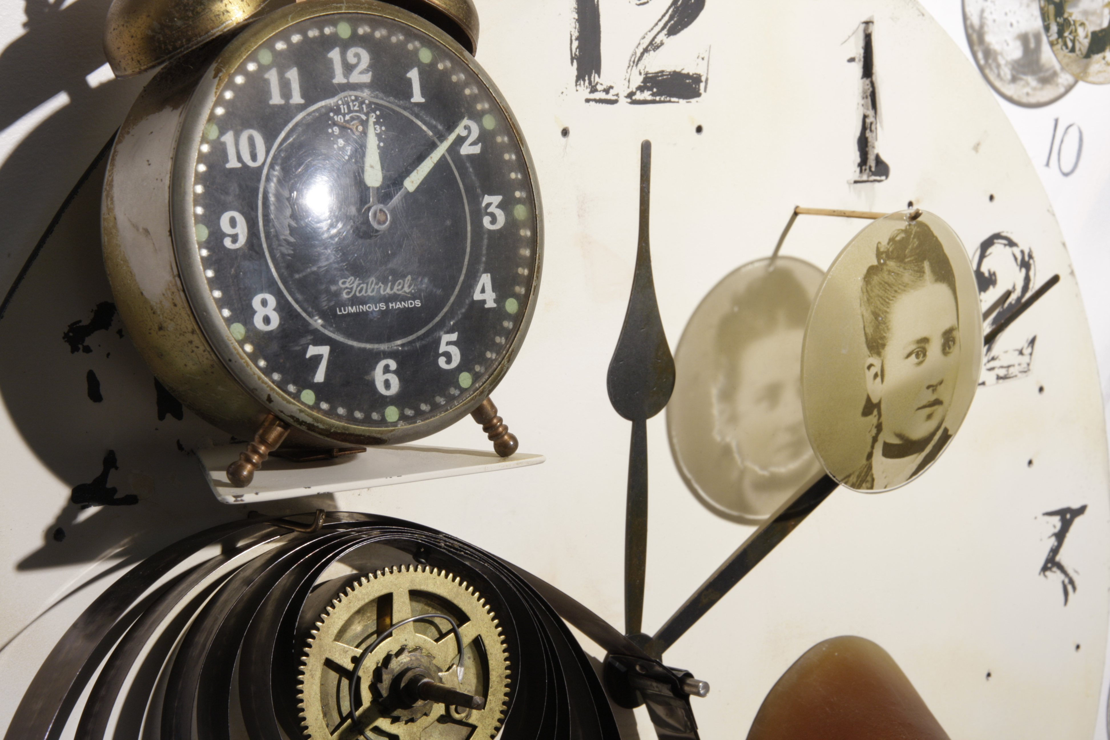 Detail of 3D wall piece painting with 16 photos of people on glass, glass hands holding gears, and clock parts.