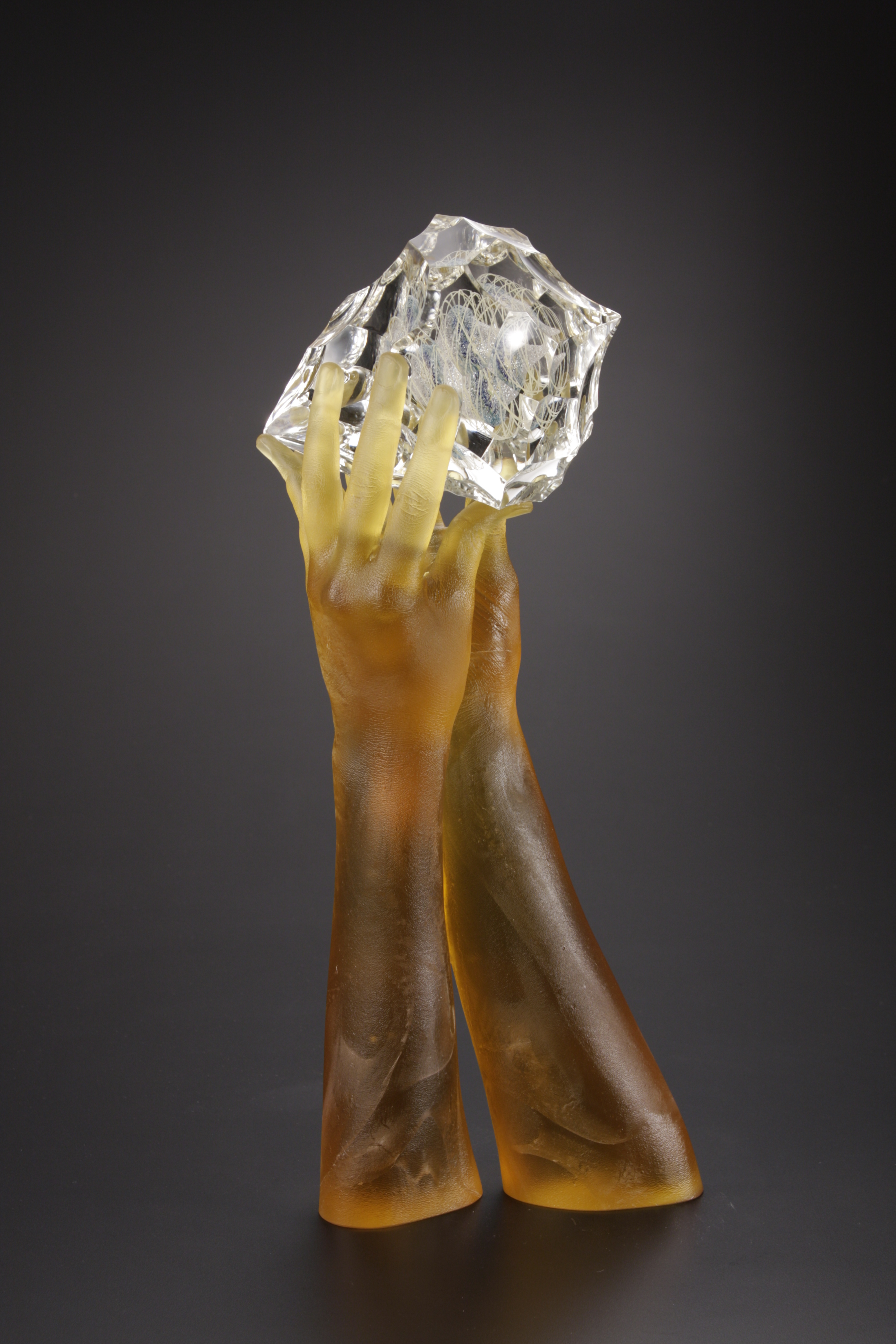 Sculpture of glass hands holding lens cut jewel.