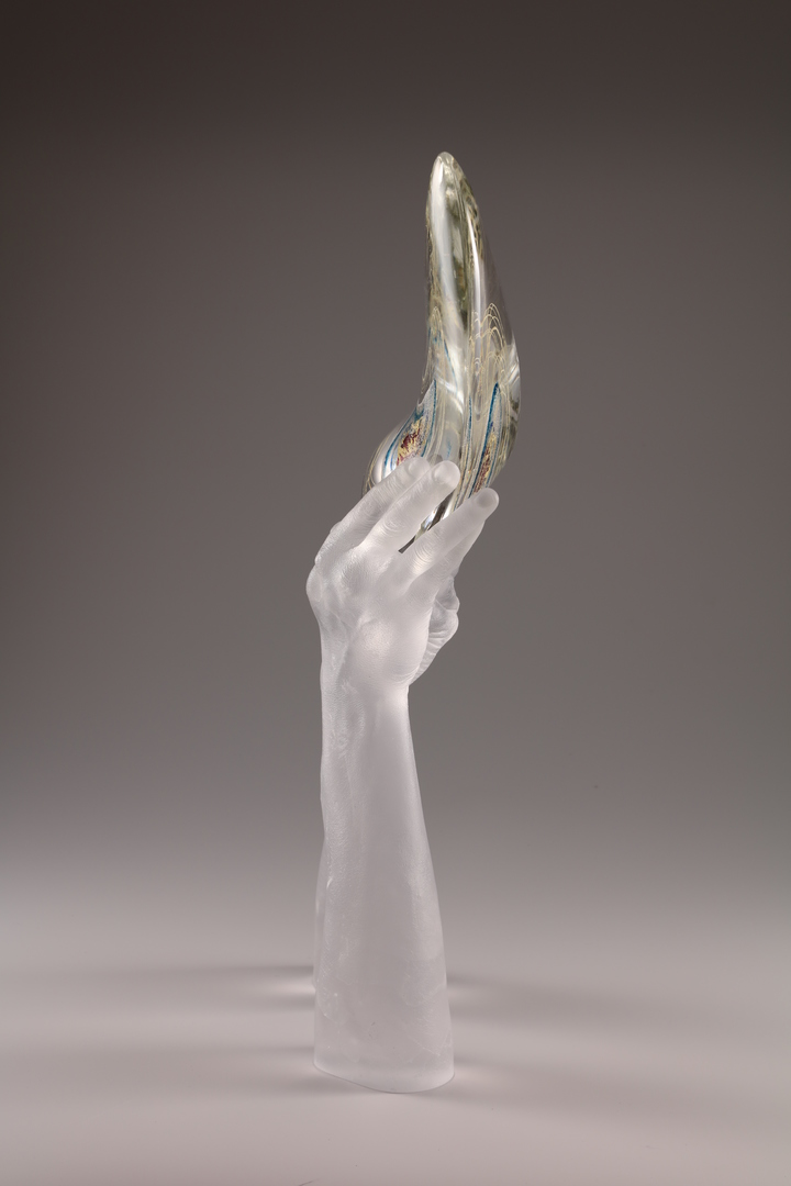 Sculpture of hands cast in glass holding curved teardrop form, side view.
