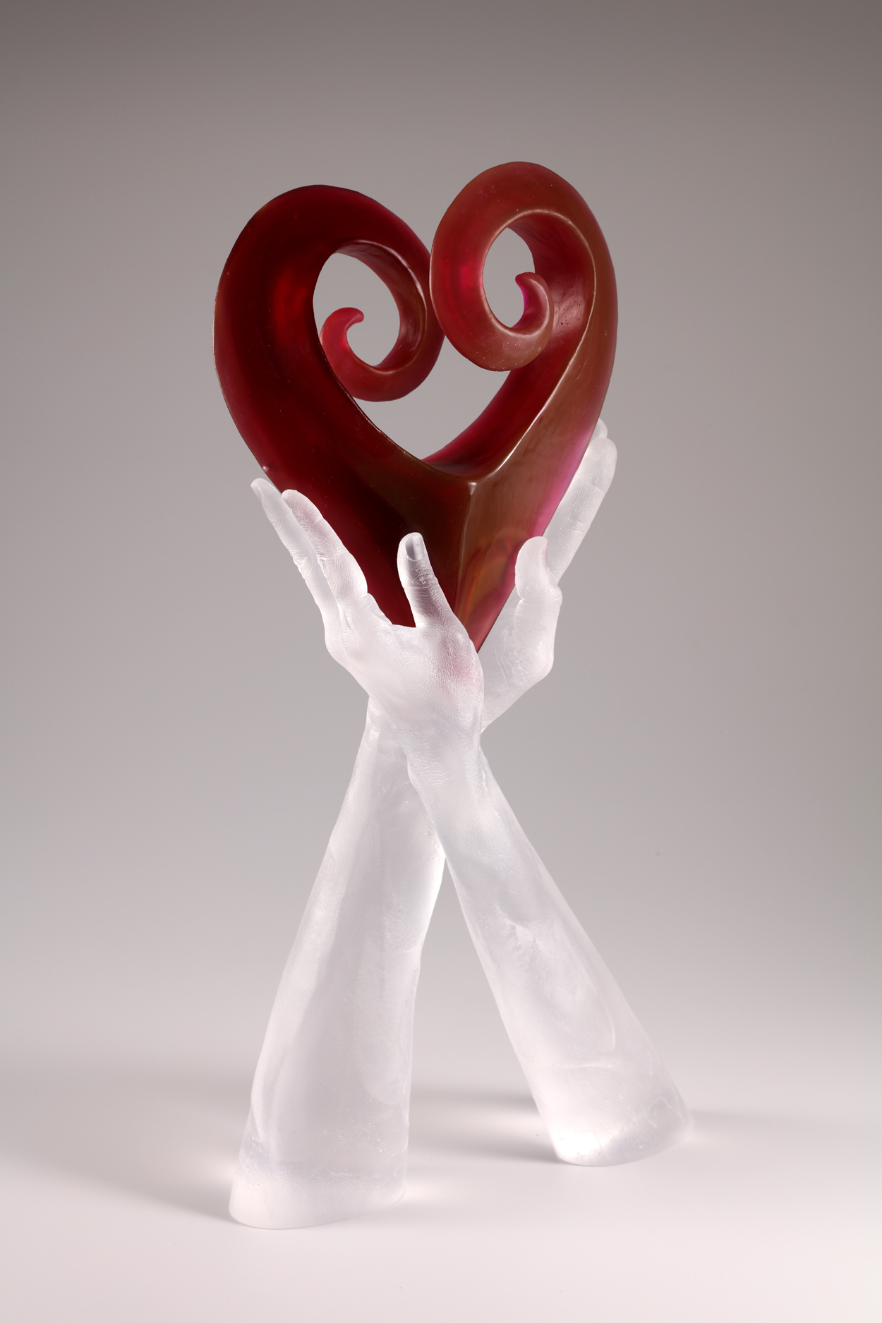 Two hands cast in clear glass holding ruby cast heart.