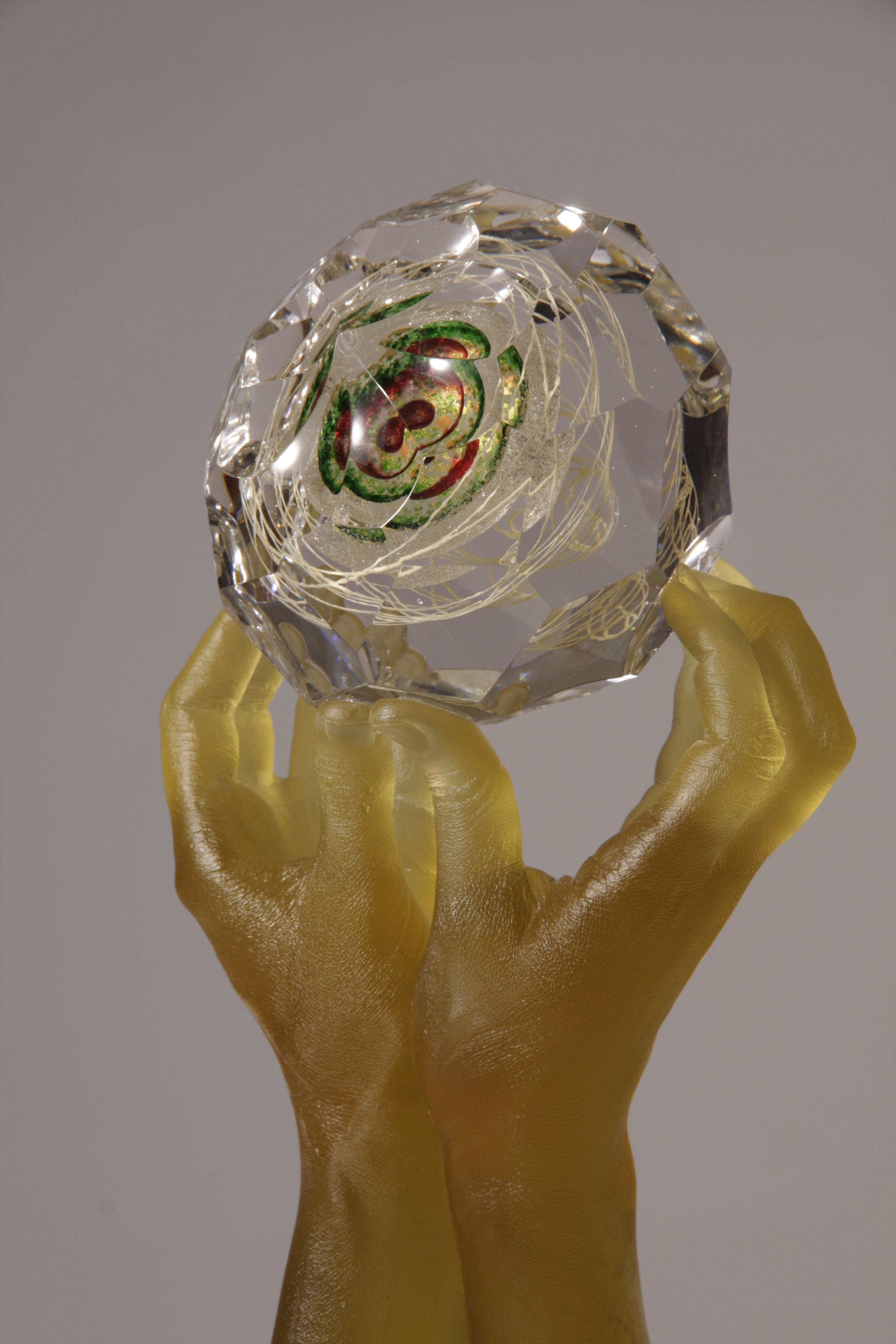 Close-up of sculpture of glass hands holding faceted glass gem, center of ruby, green, gold, and mica.