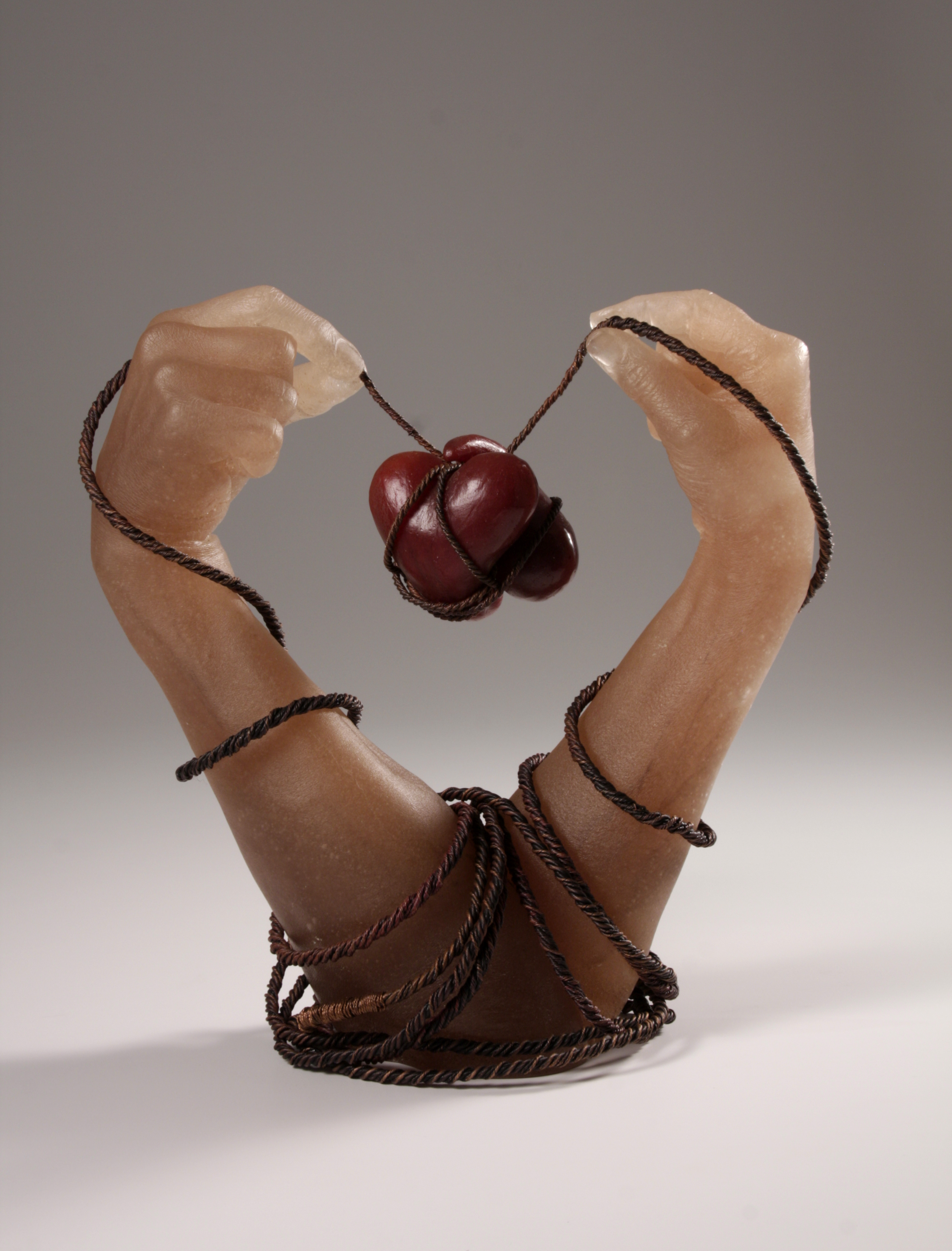 Sculpture of glass hands holding wire that binds two hearts between hands.