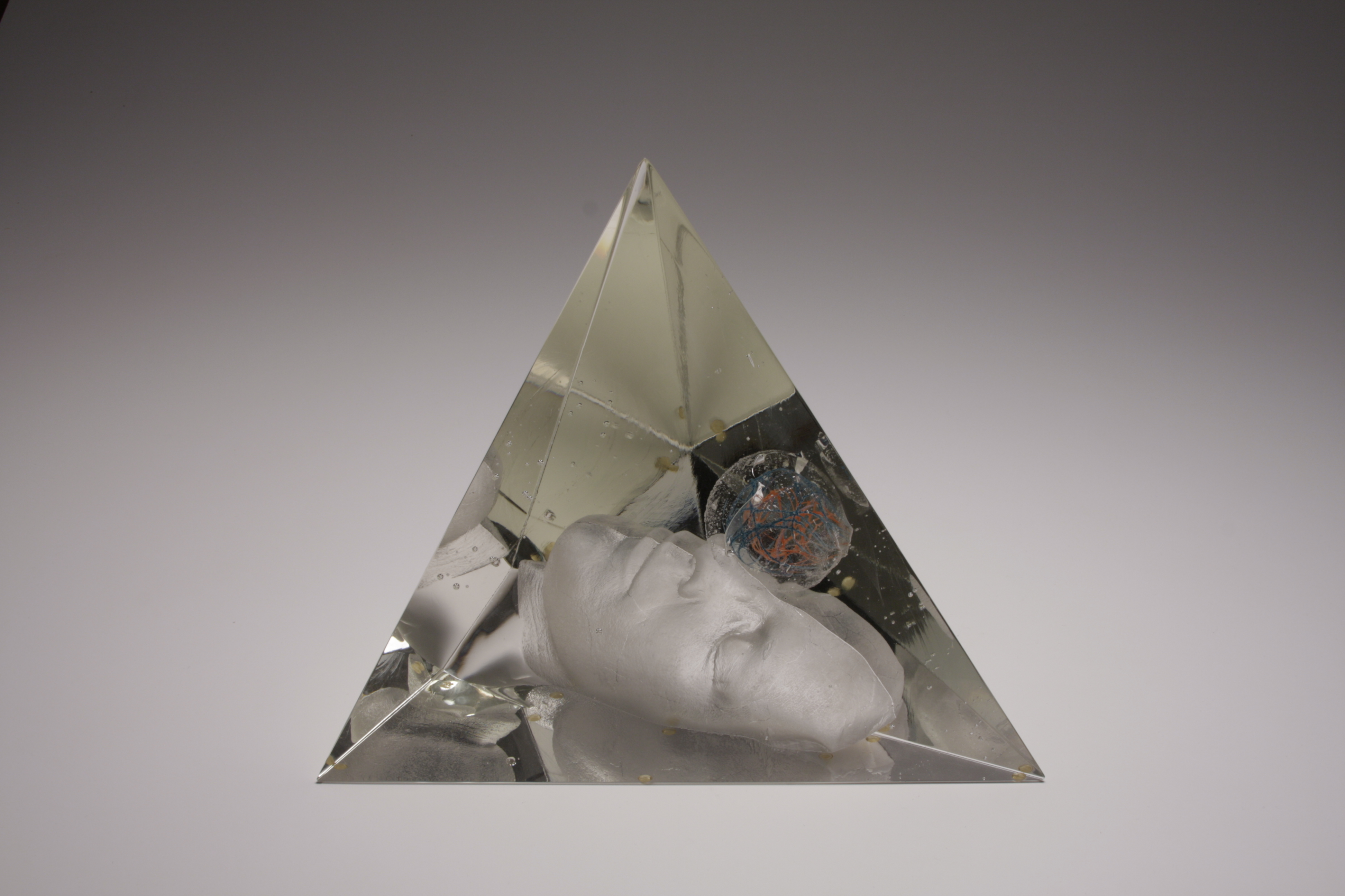 Face looking up with round object floating above it inside a glass pyramid.