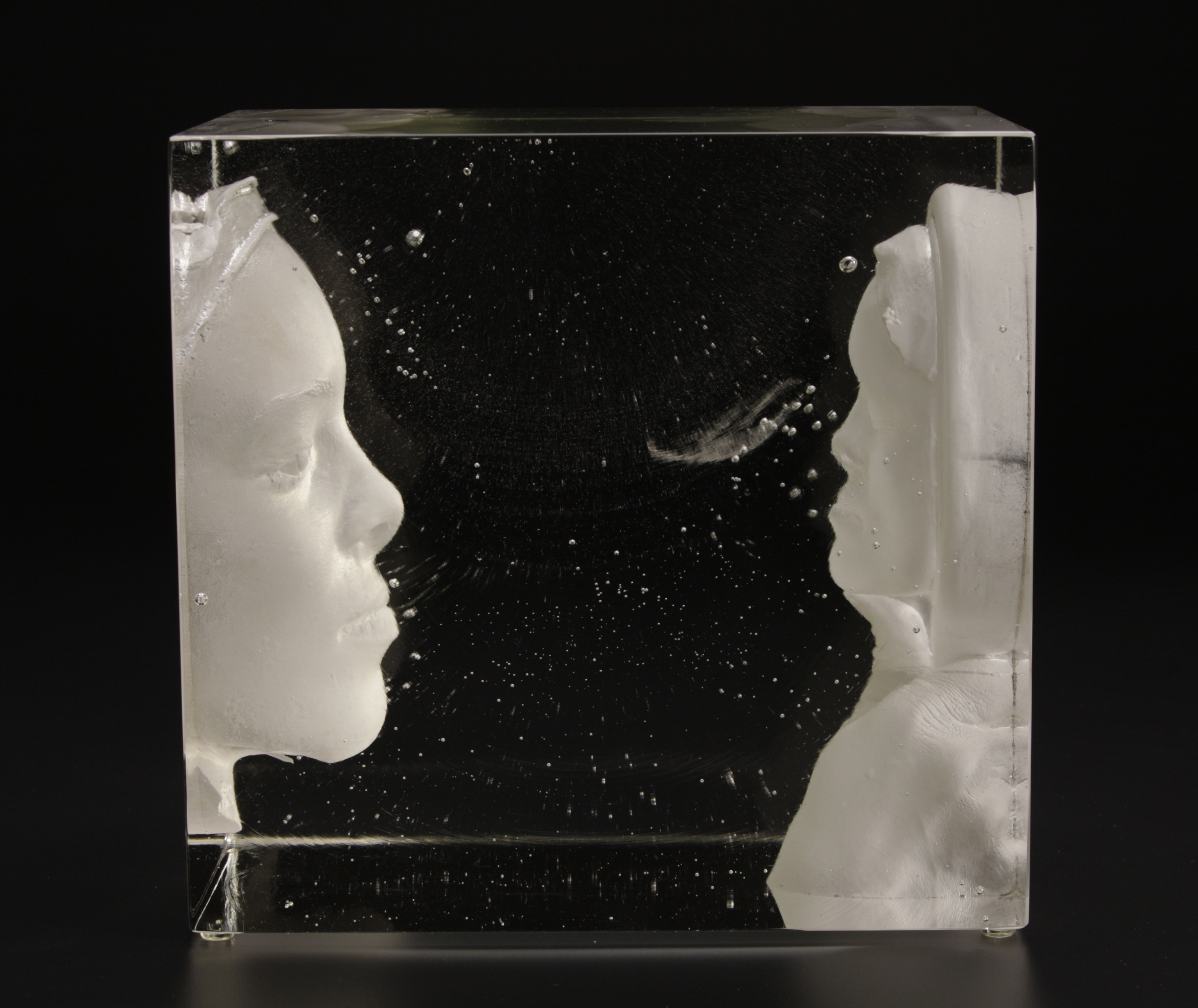 Glass block containing face with finger in front of it and a another face coming out of the block.Cast glass block with face looking in the mirror.