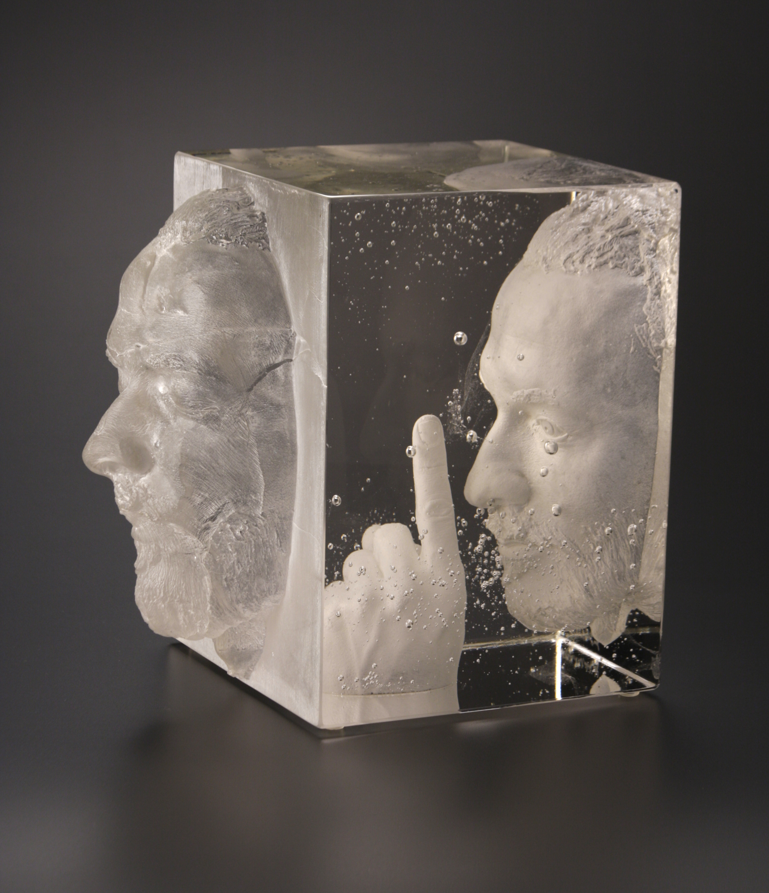 Glass block containing face with finger in front of it and a another face coming out of the block.