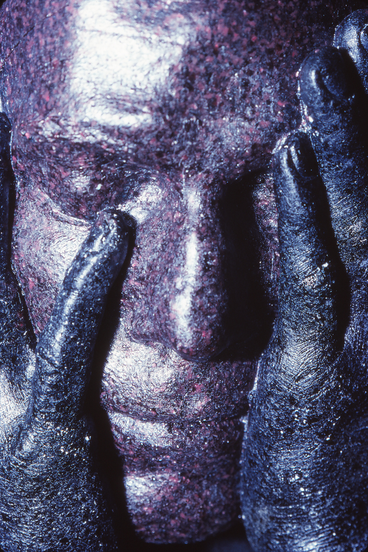 Close-up of cast glass sculpture of face with hands.