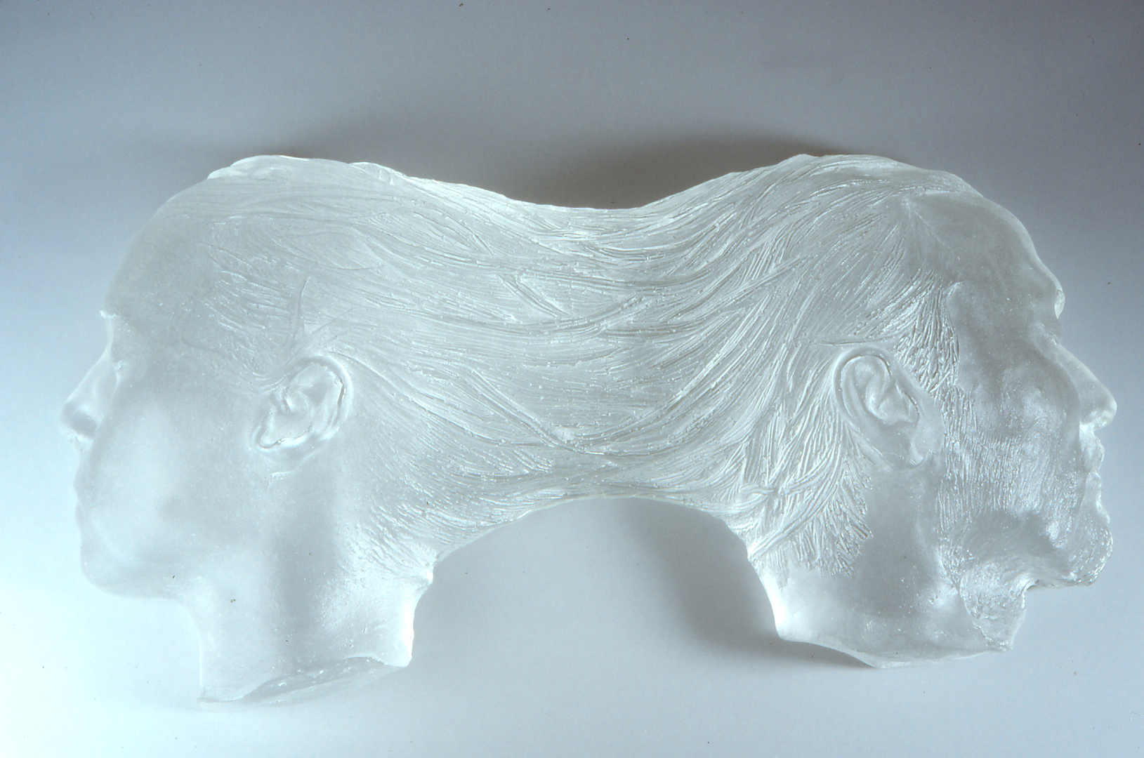 Sculpture of two heads connected at the back by hair flowing between them.