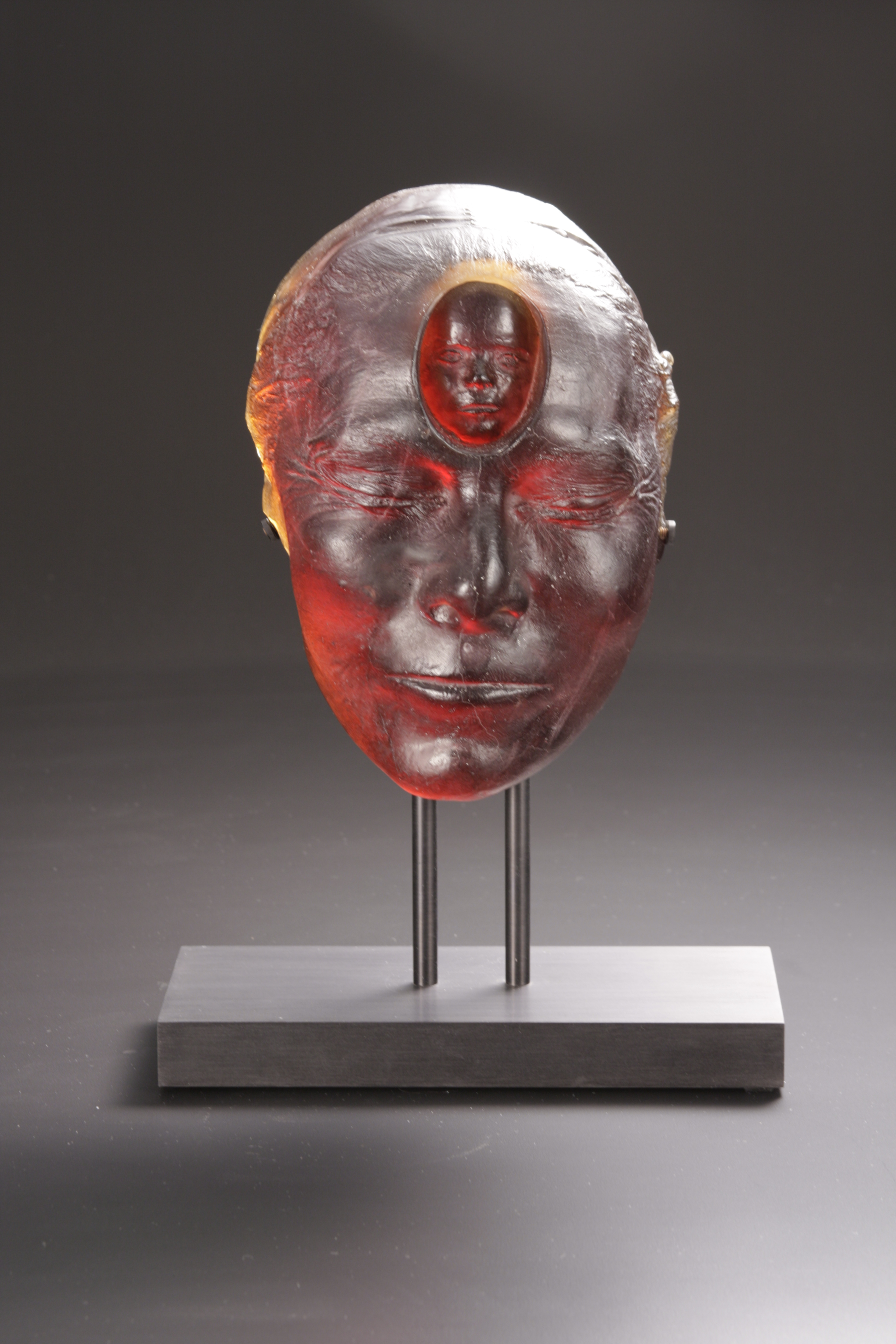 Sculpture of women's head with small child's face in forehead on black metal stand.