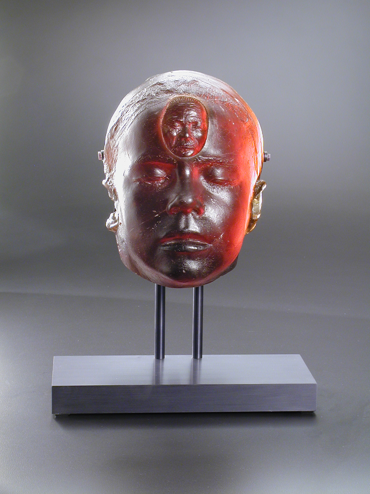 Sculpture of face with small head in forehead on metal stand.