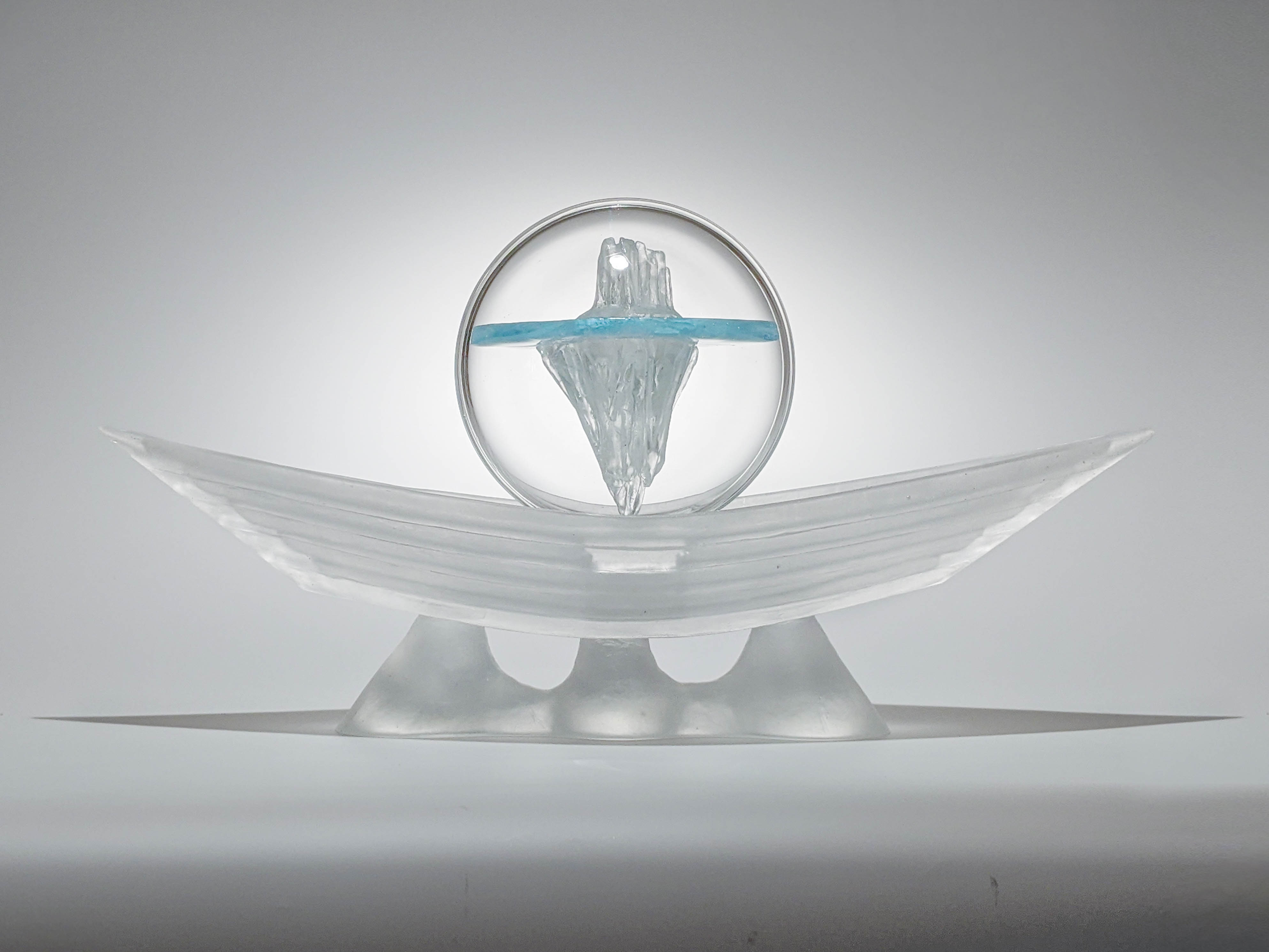 Sculpture of glass boat with iceberg.