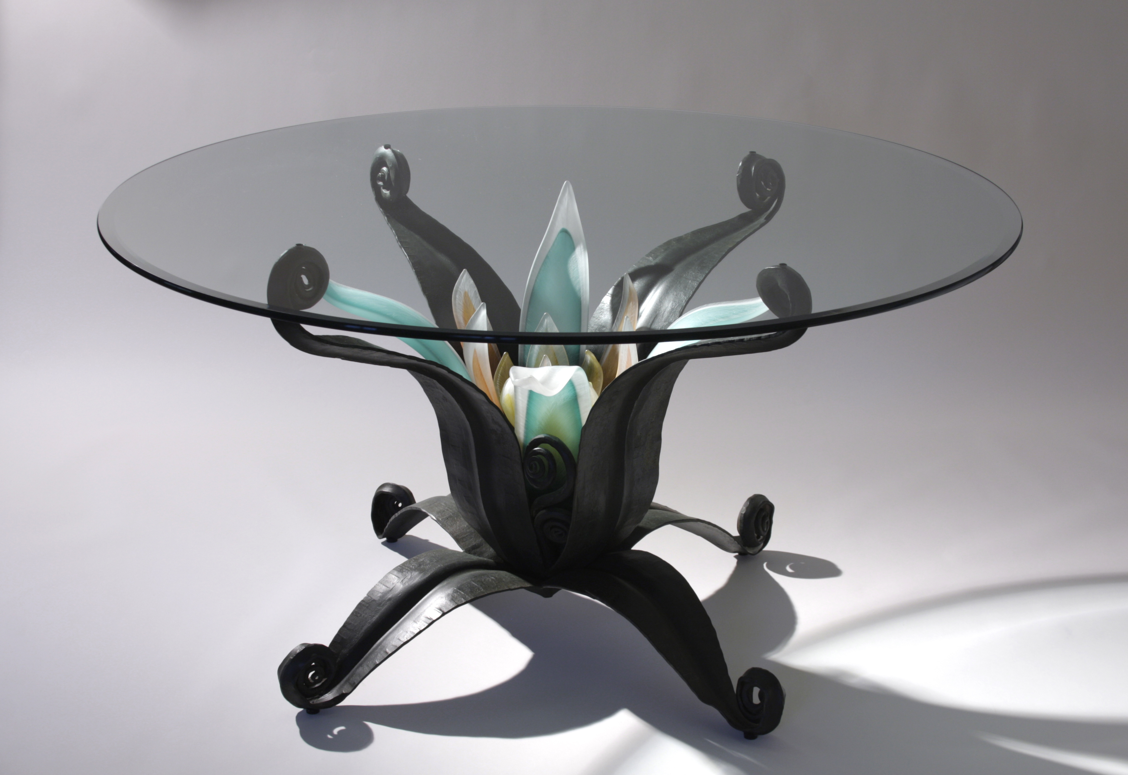 Table with clear glass top, flower center surrounded by forged steel base.