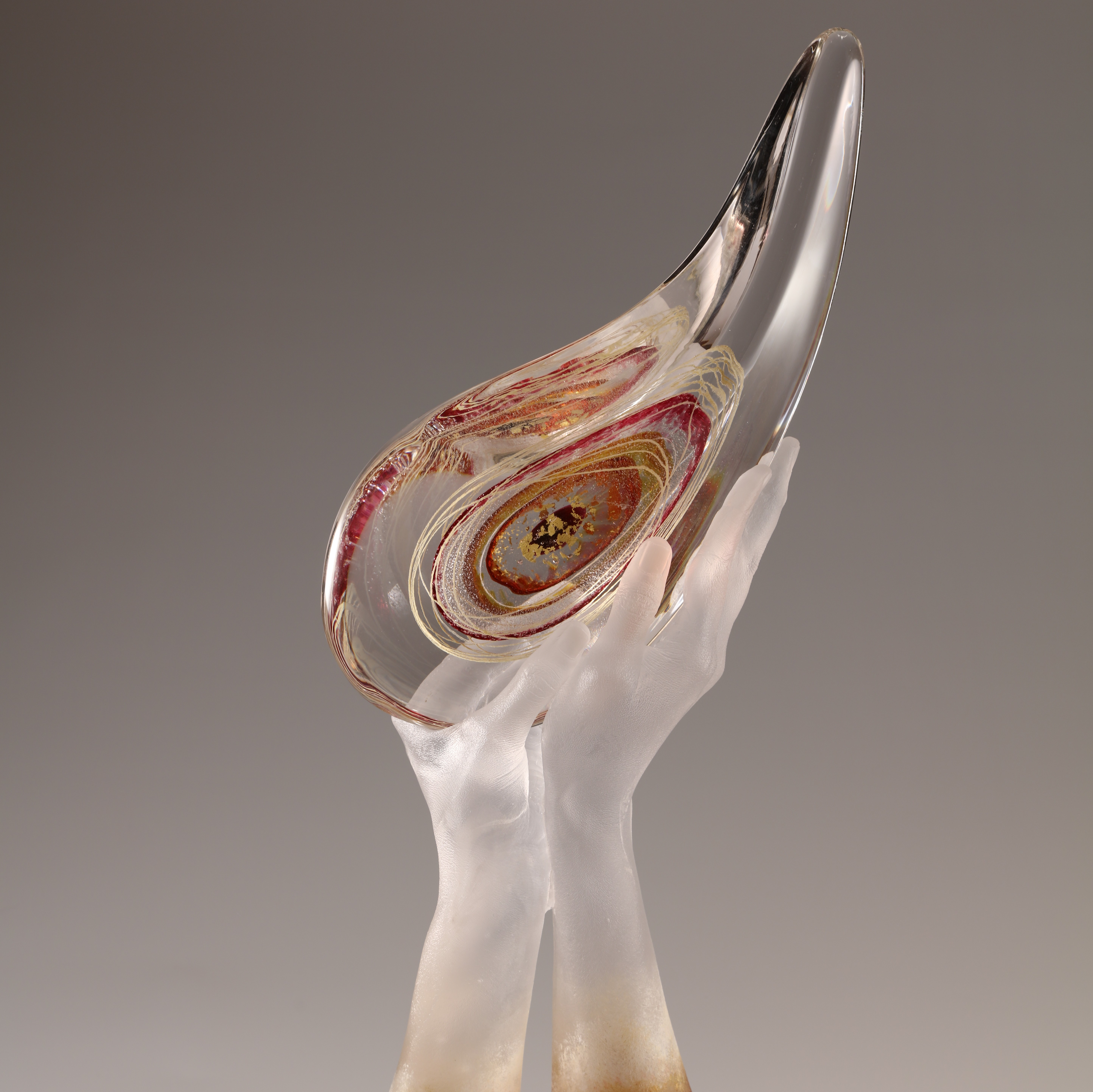 Sculpture of hands cast in glass holding curved teardrop form.
