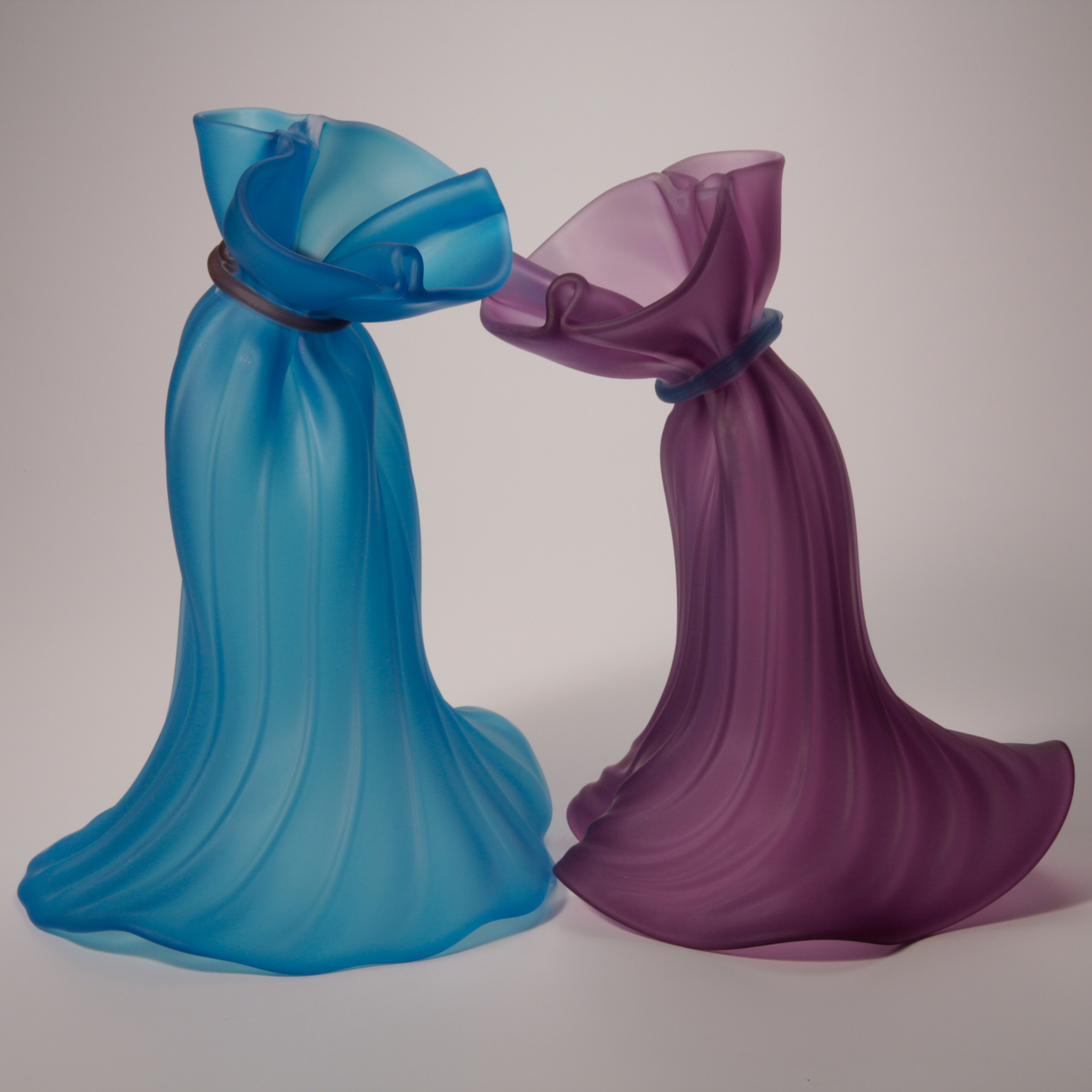 A pair of glass fabric-like forms alluding to dancers in blue and purple.