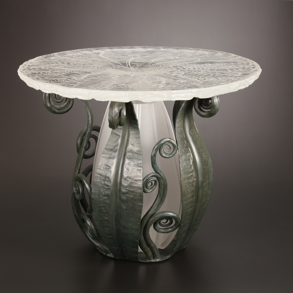 Table with clear top with fern pattern, base of table glass form surrounded by steel vines.
