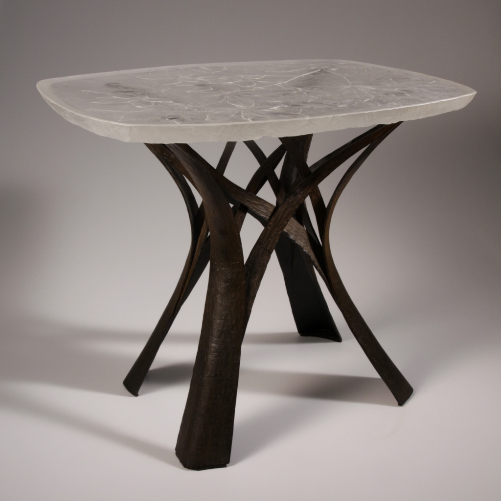 Table with clear glass top with pattern of buckeye leaves, base of forged steel.