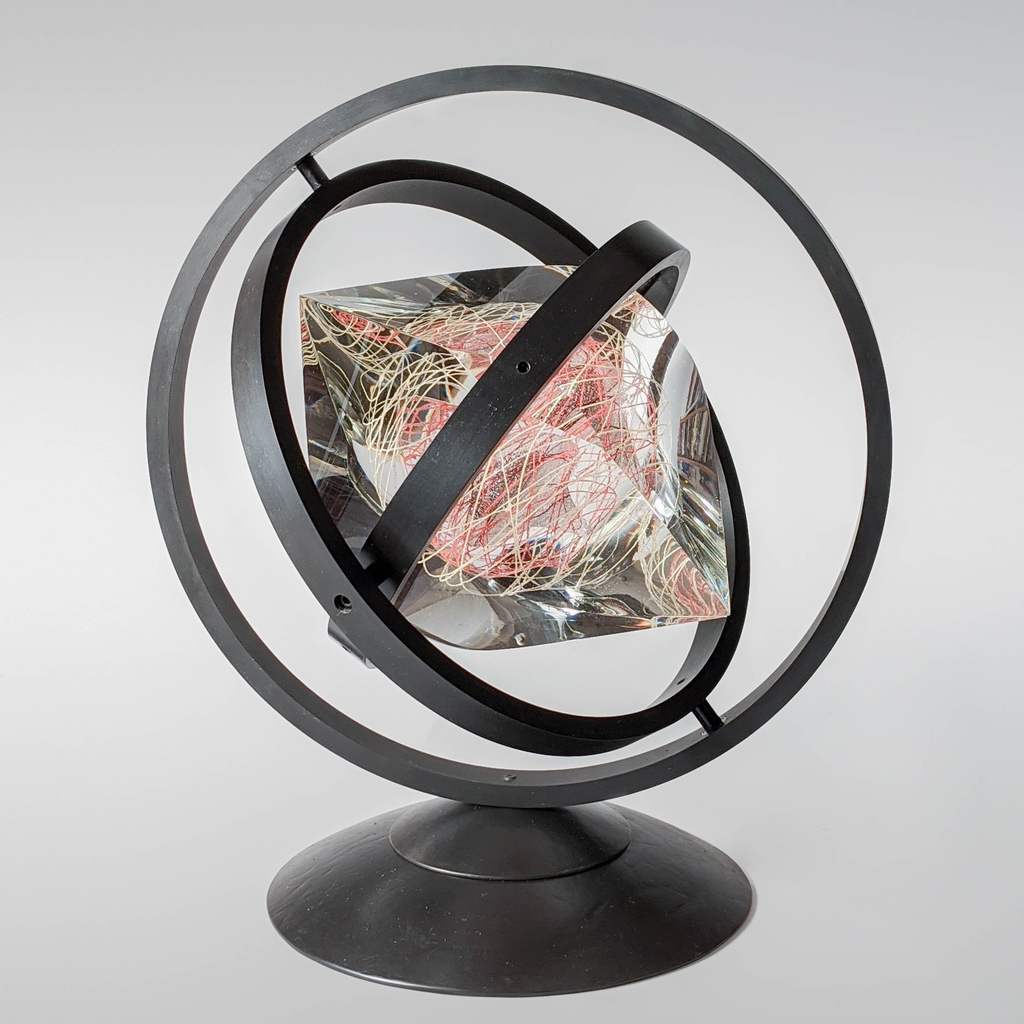 Glass gem that spins in metal rings.
