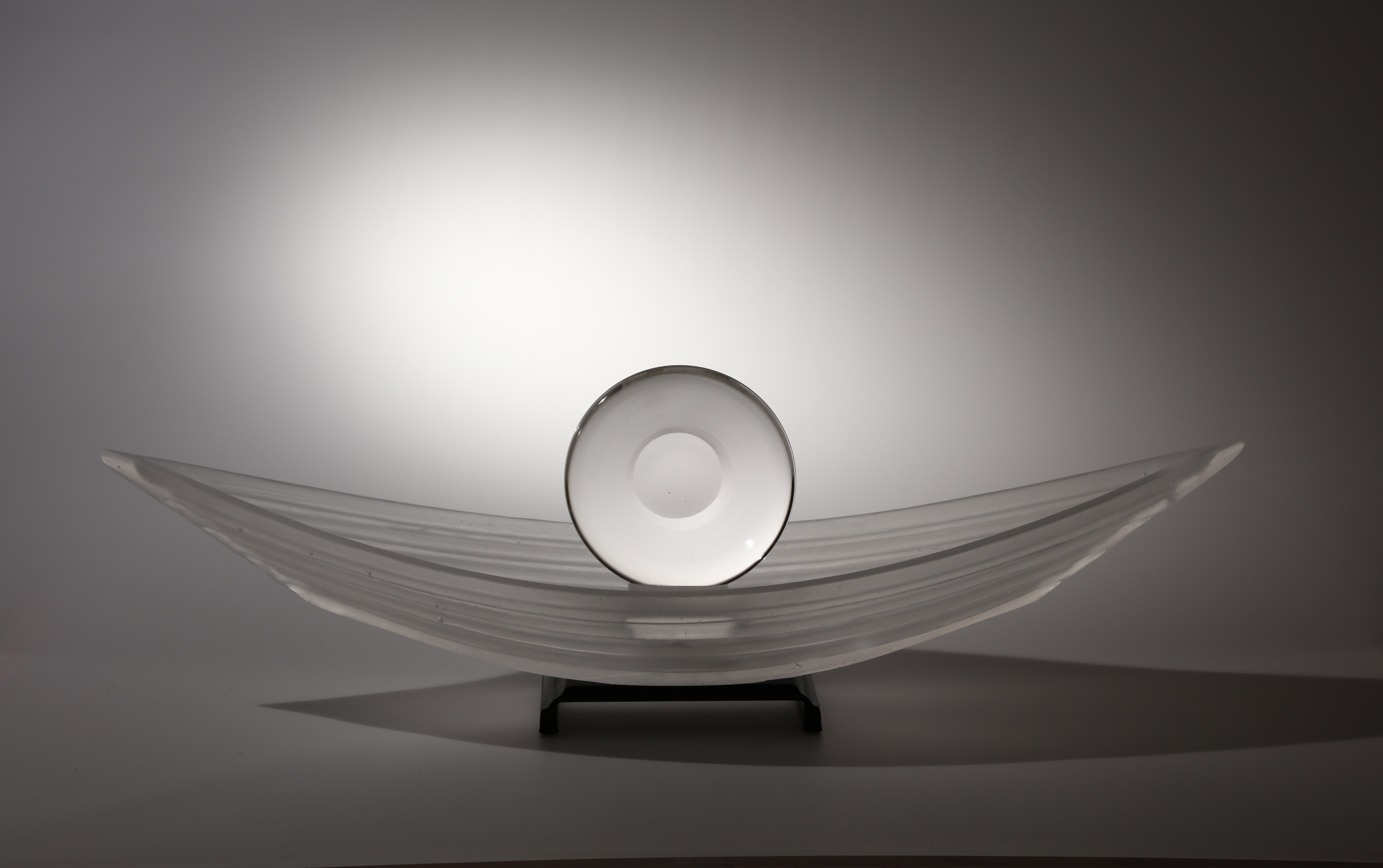 Sculpture of glass boat with glass disk in it.