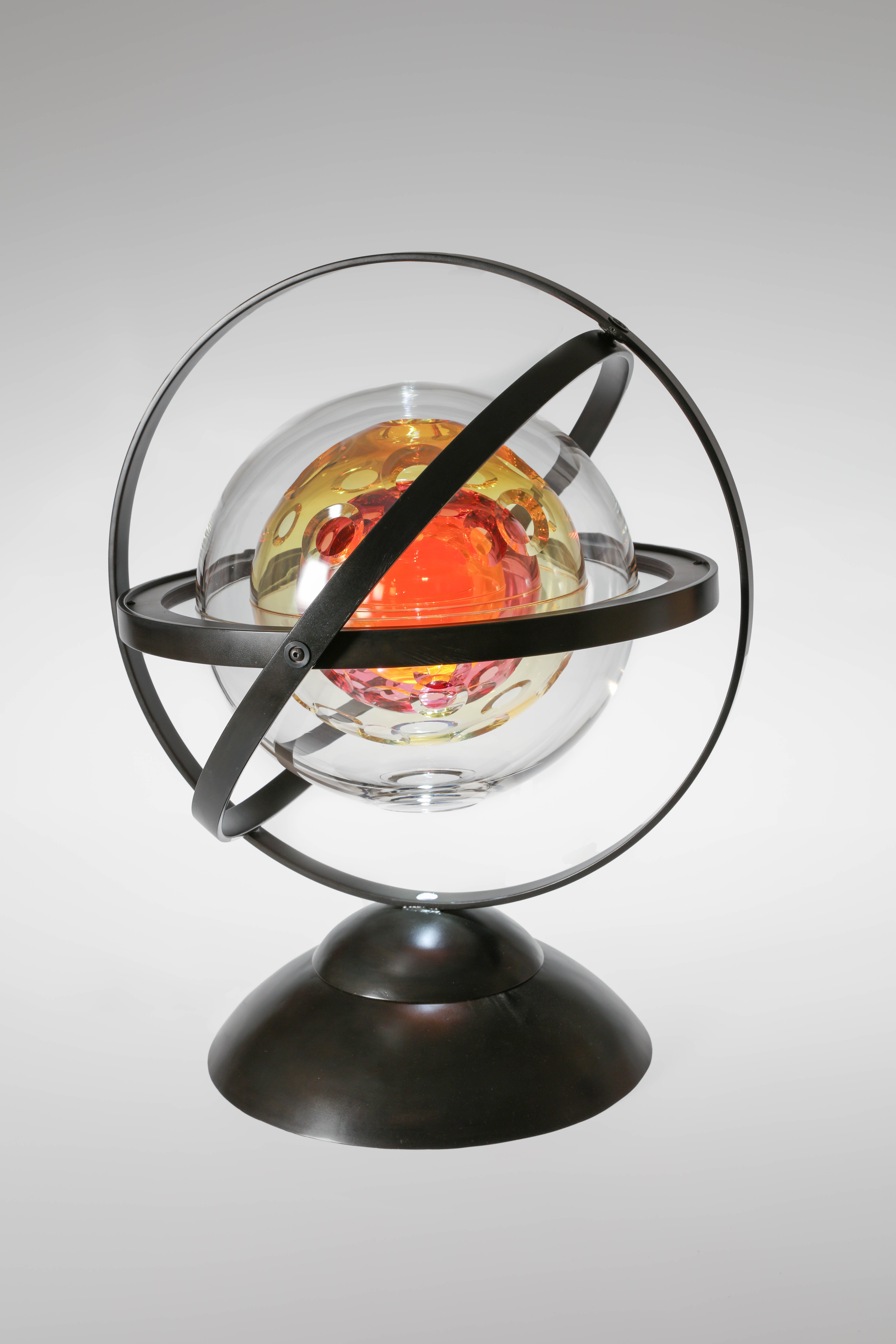 Glass sphere that spins in metal rings.