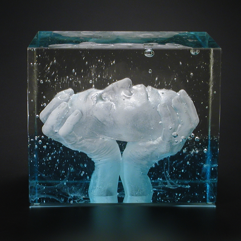 Aqua blue and clear glass block containing face held up by hands.
