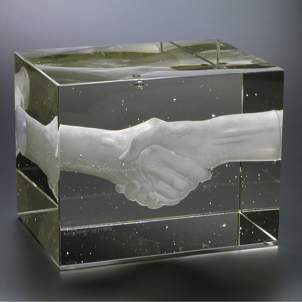 Clear glass block containing two female hands clasped in a handshake.