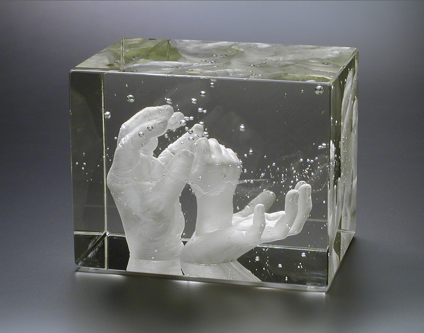Clear glass block containing three generations of hands.