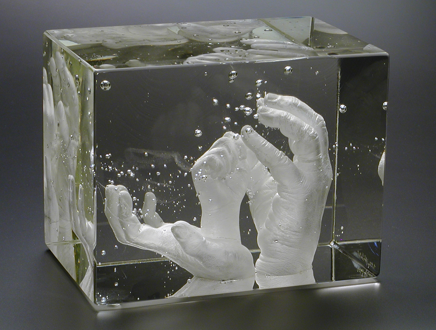 Alternate view of clear glass block containing three generations of hands.