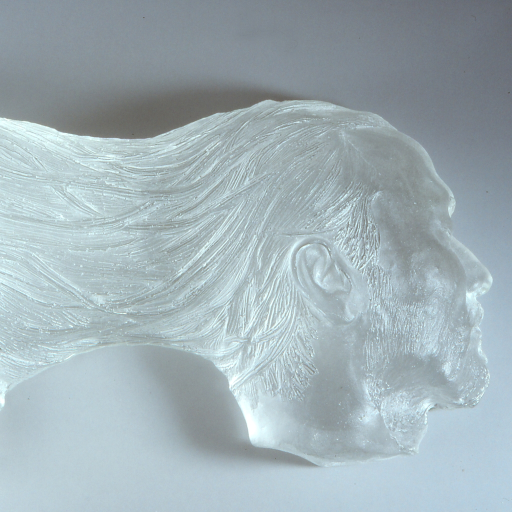 Close-up of sculpture of two heads connected at the back by hair flowing between them.