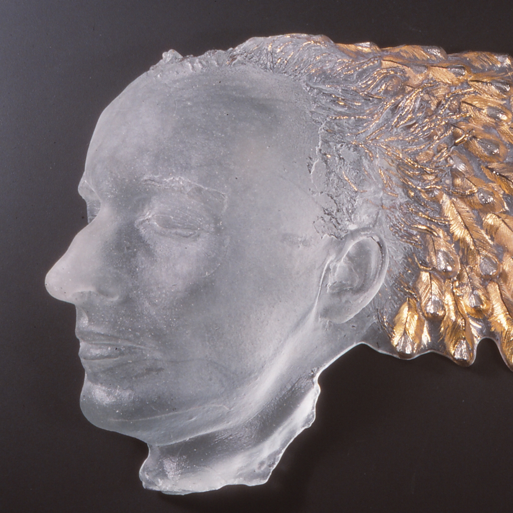 Sculpture of head with wing coming out of the back.
