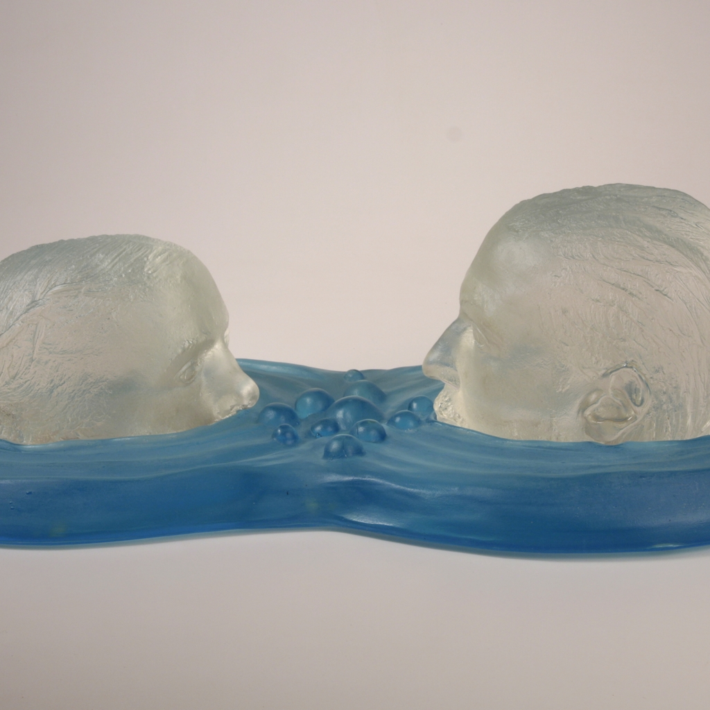 Sculpture in glass of two clear heads blowing bubbles in blue water.