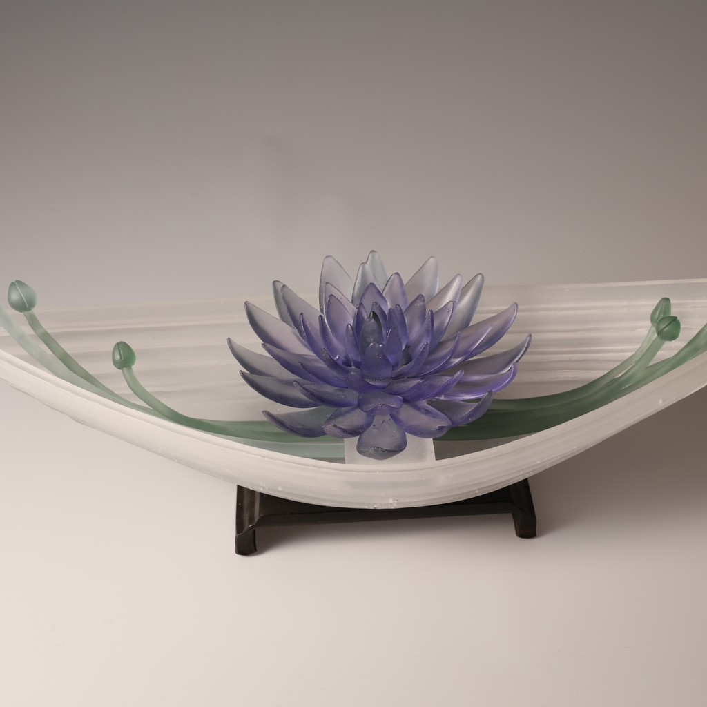 Sculpture of cast glass boat and indigo flowers on steel base.