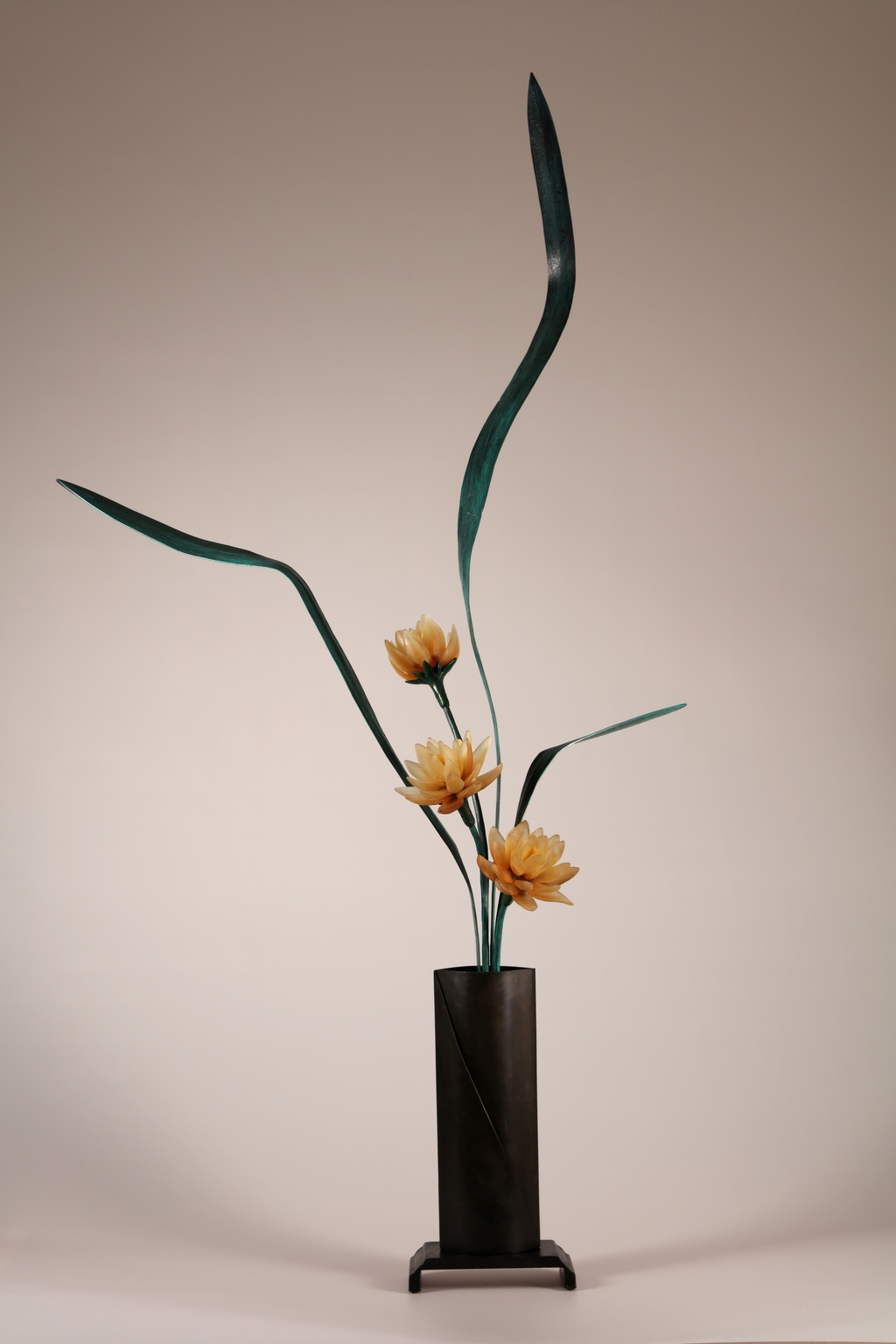 Left side of sculptural flower arrangement in cast glass with amber flowers, green steel leaves, tall vase in deep brown.