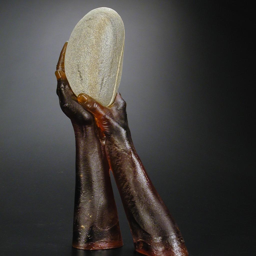 Sculpture of cast glass hands holding grey stripped rock.