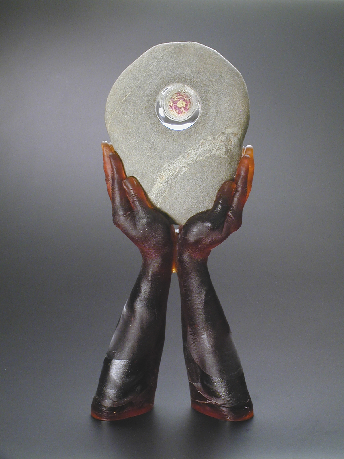 Sculpture of hands cast in red brown glass holding a grey and white rock with a portal in it.