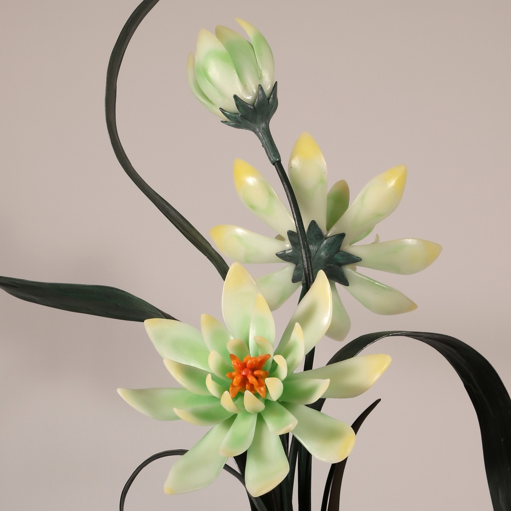 Close up of sculptural flower arrangement in cast glass of yellow-green with orange centers in a brown vase.