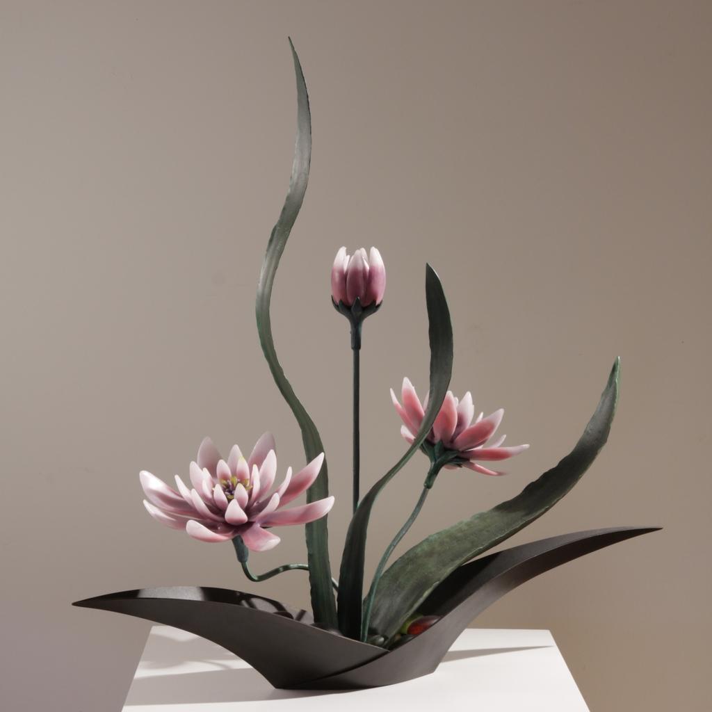 Sculptural flower arrangement in cast glass with pink flowers, green steel leaves, boat shaped vase in deep brown.
