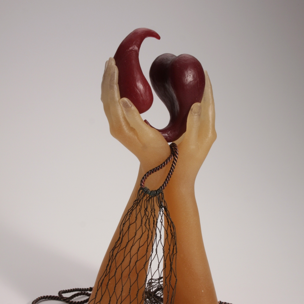 Sculpture of two hands cast in glass holding two red glass hearts with a fishing net.