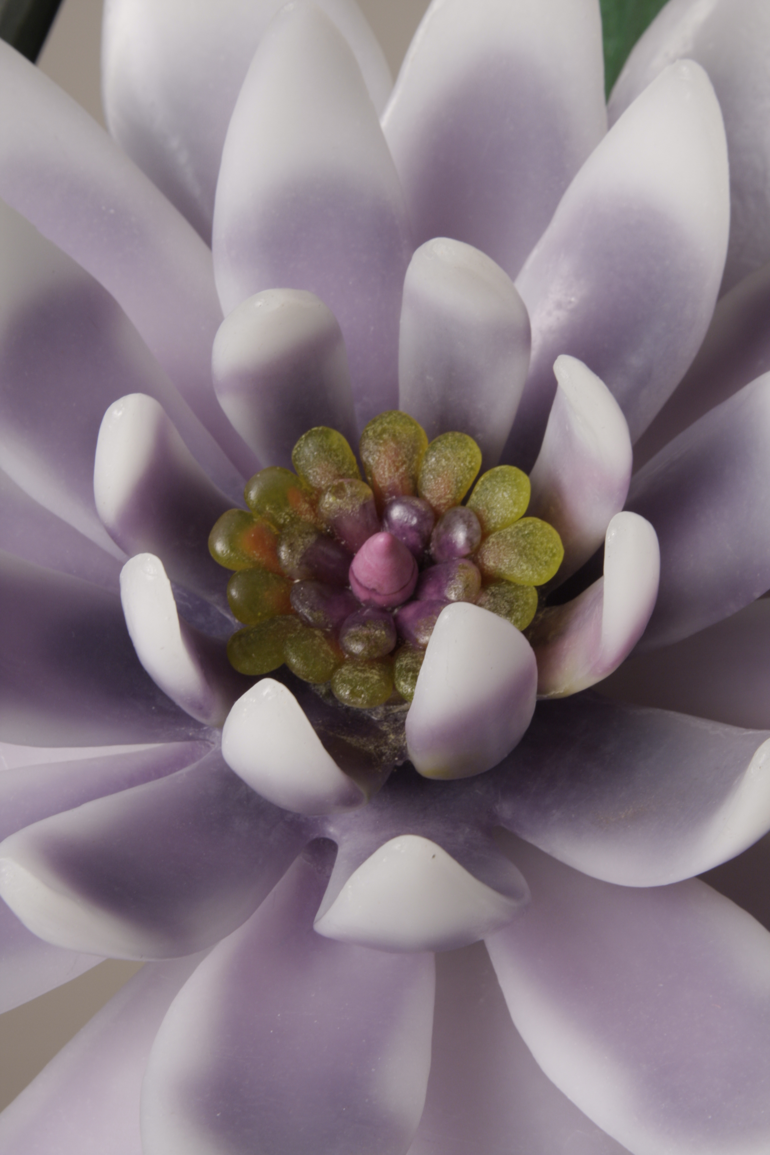 Detail of Sculptural flower arrangement in cast glass with white and lavender flower.