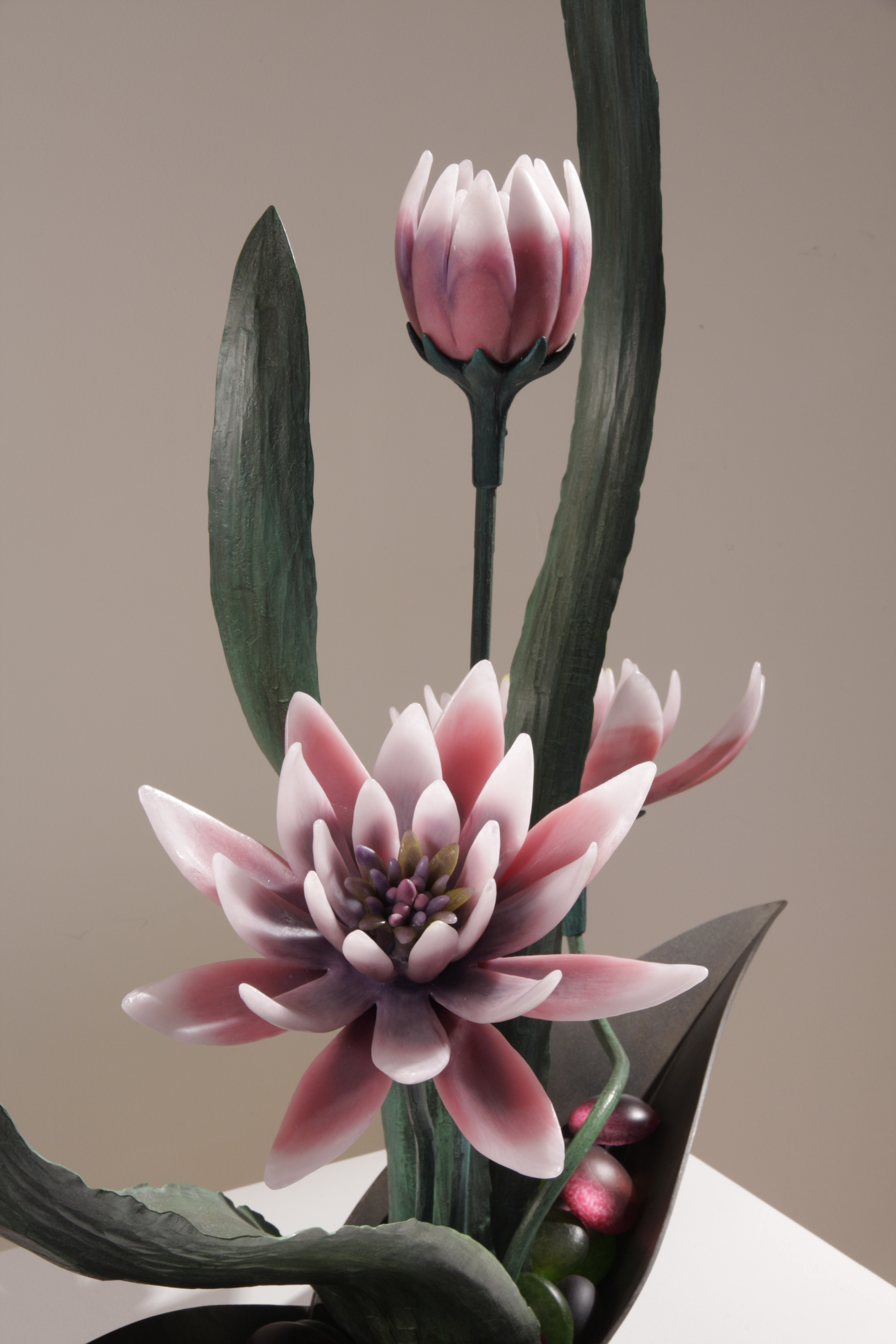 Close up of sculptural flower arrangement in cast glass with pink flowers, green steel leaves, boat shaped vase in deep brown.