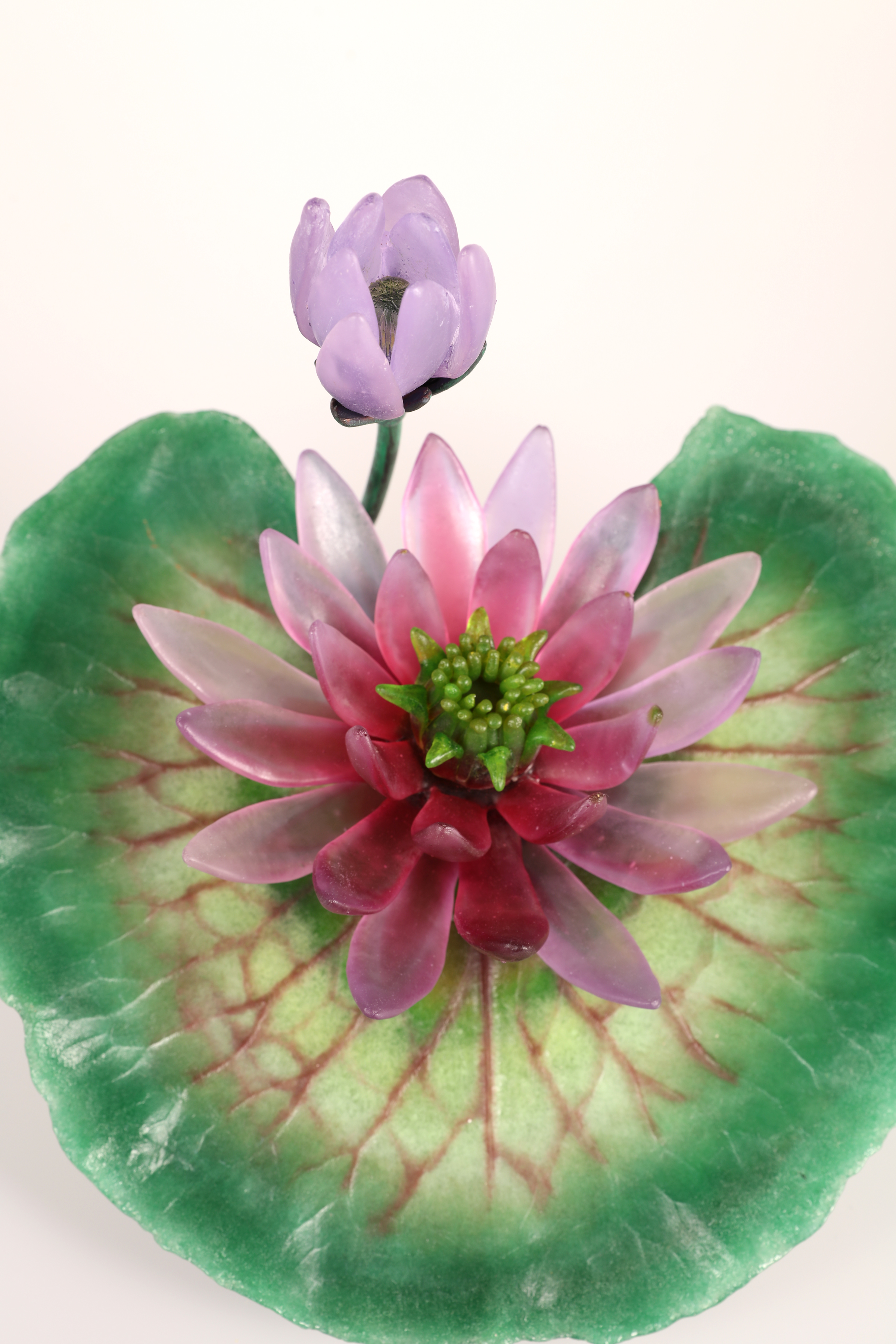 Top view of glass water lily in ruby and green.