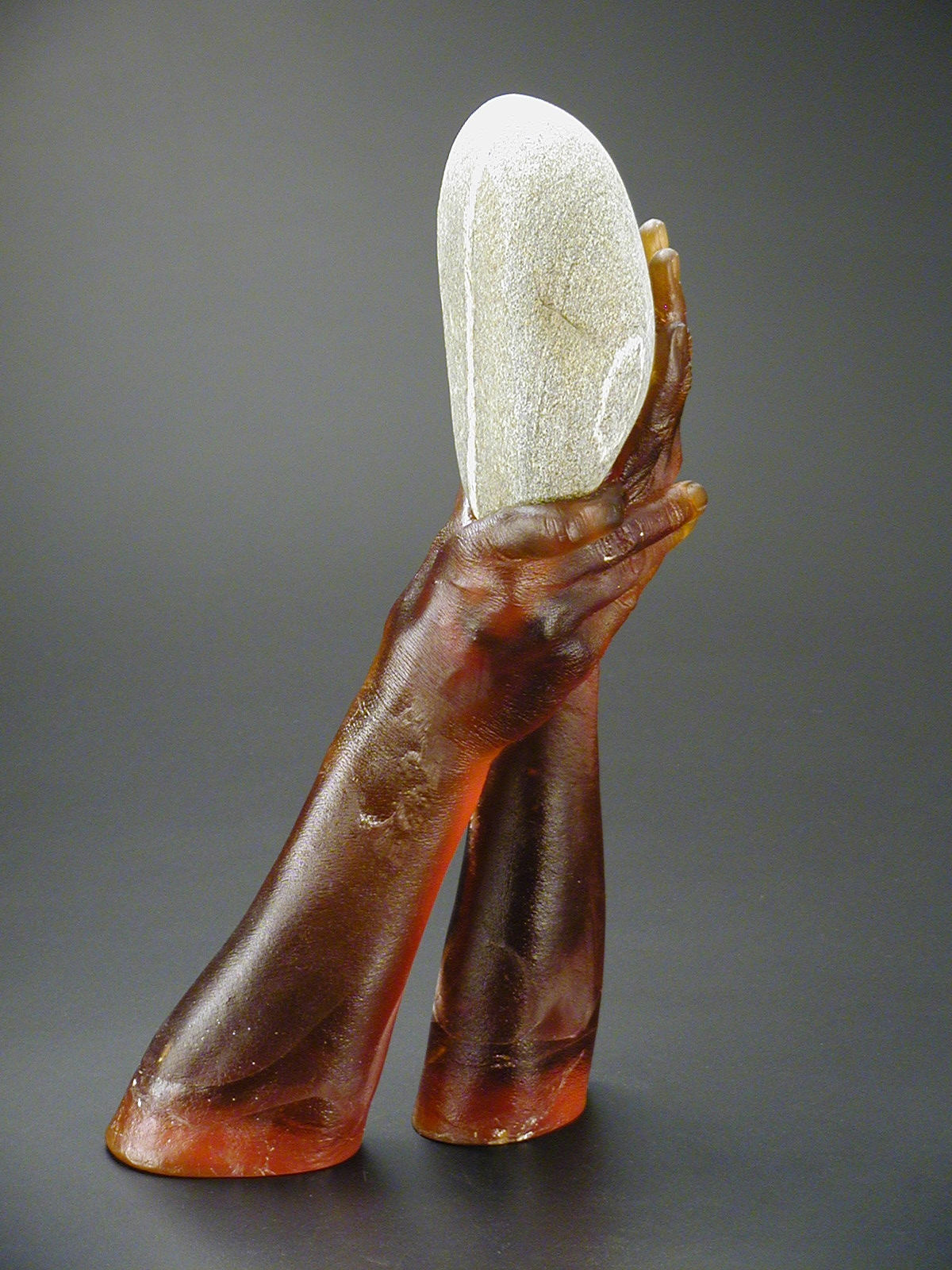 Side view of sculpture of cast glass hands holding grey stripped rock.