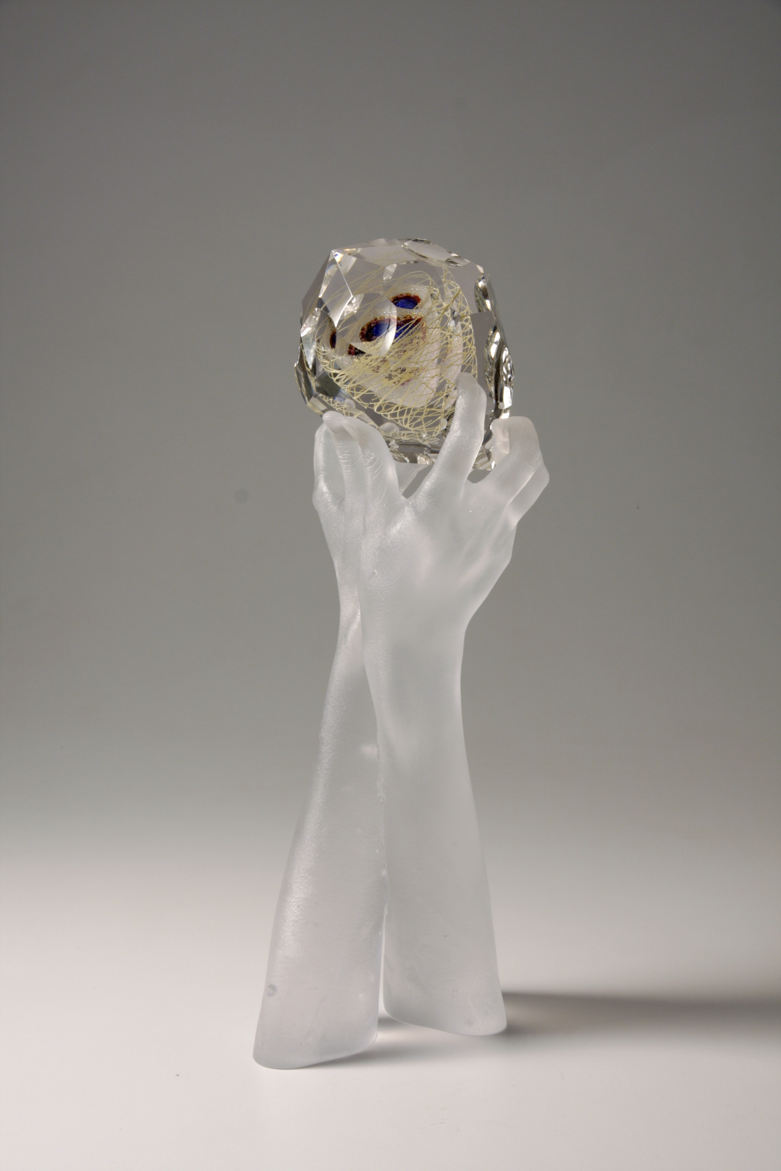 Side view of sculpture of clear glass hands holding faceted glass gem containing blue, purple, ruby, gold, and mica.