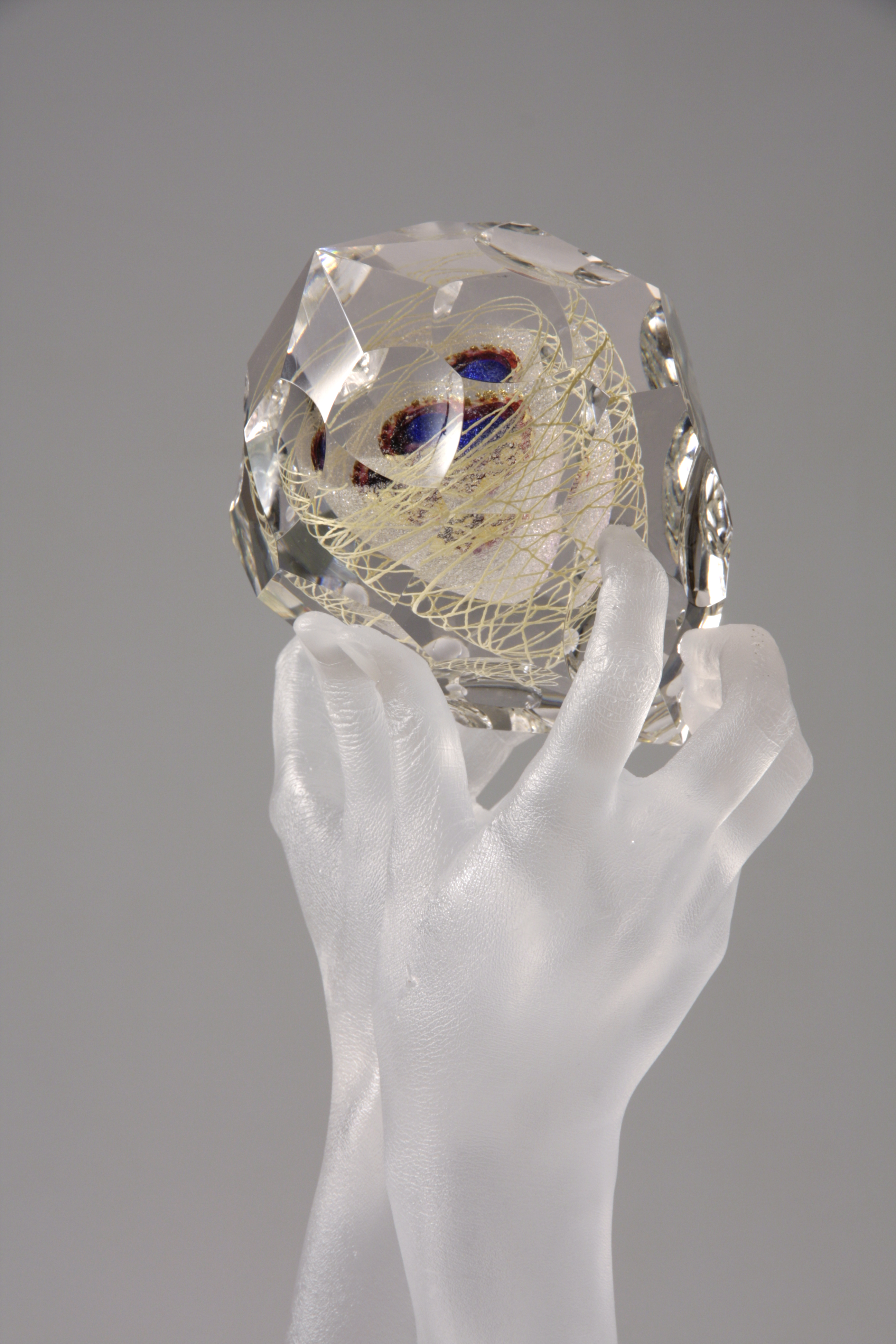 Close-up of sculpture of clear glass hands holding faceted glass gem containing blue, purple, ruby, gold, and mica.
