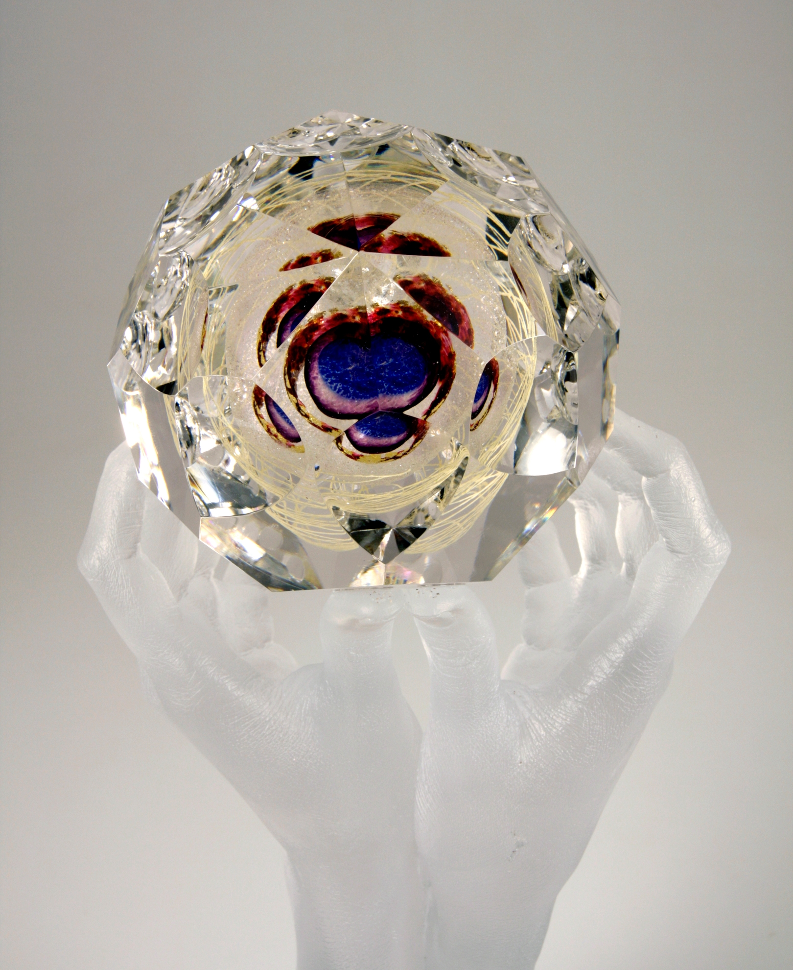 Detail of sculpture of clear glass hands holding faceted glass gem containing blue, purple, ruby, gold, and mica.