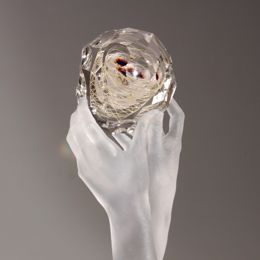 Sculpture of clear glass hands holding faceted glass gem containing blue, purple, ruby, gold, and mica.