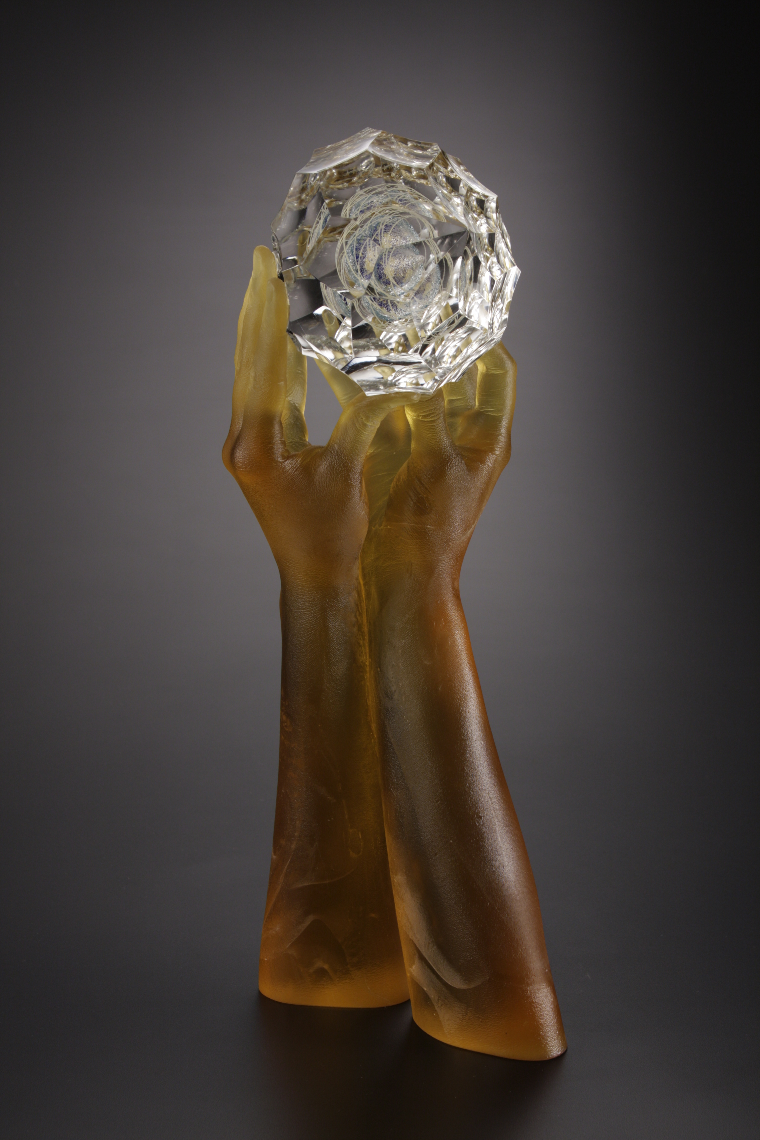 Side view of sculpture of glass hands holding lens cut jewel.