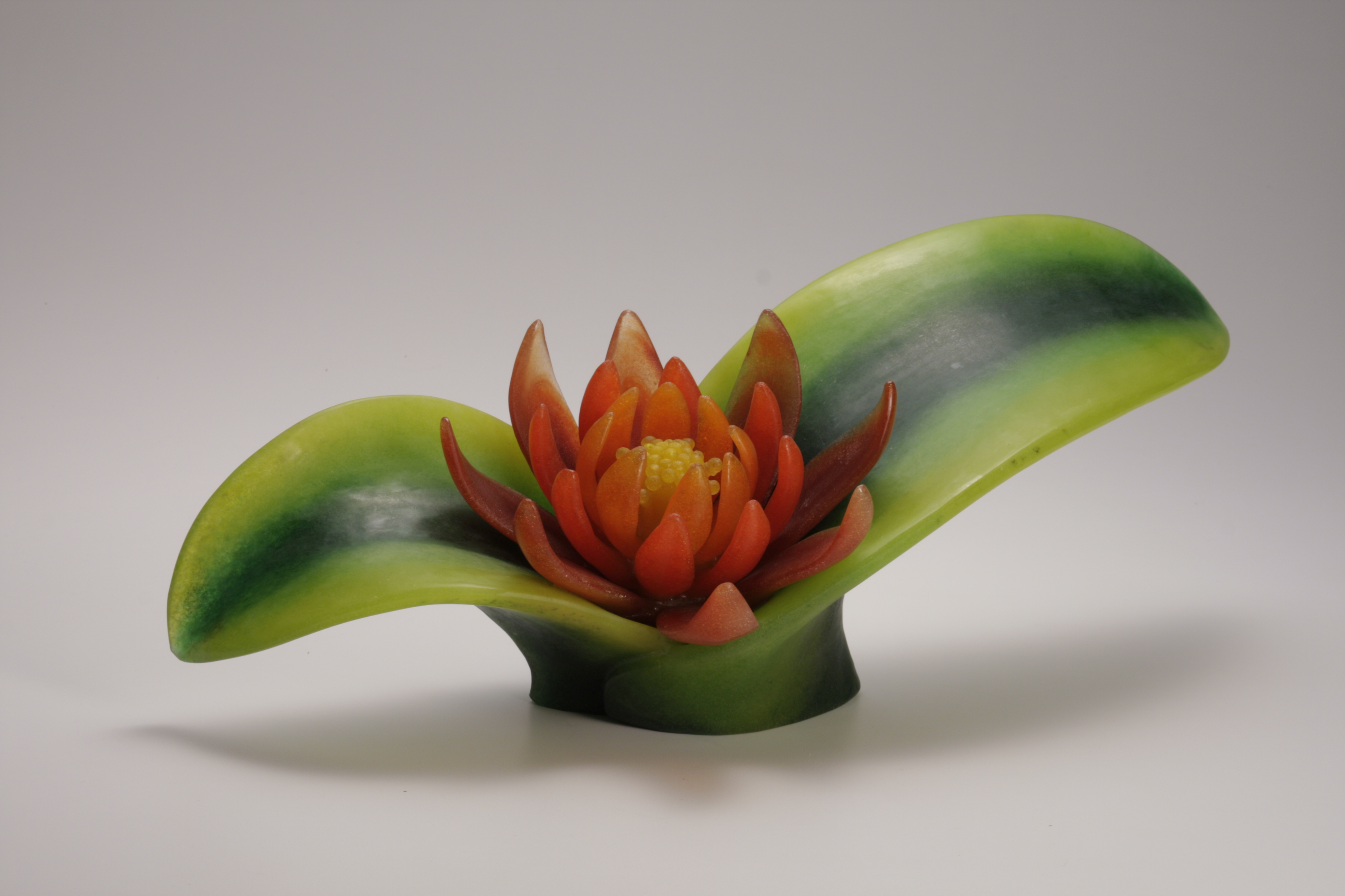 Cast glass succulent plant with with orange flower in green leaves.