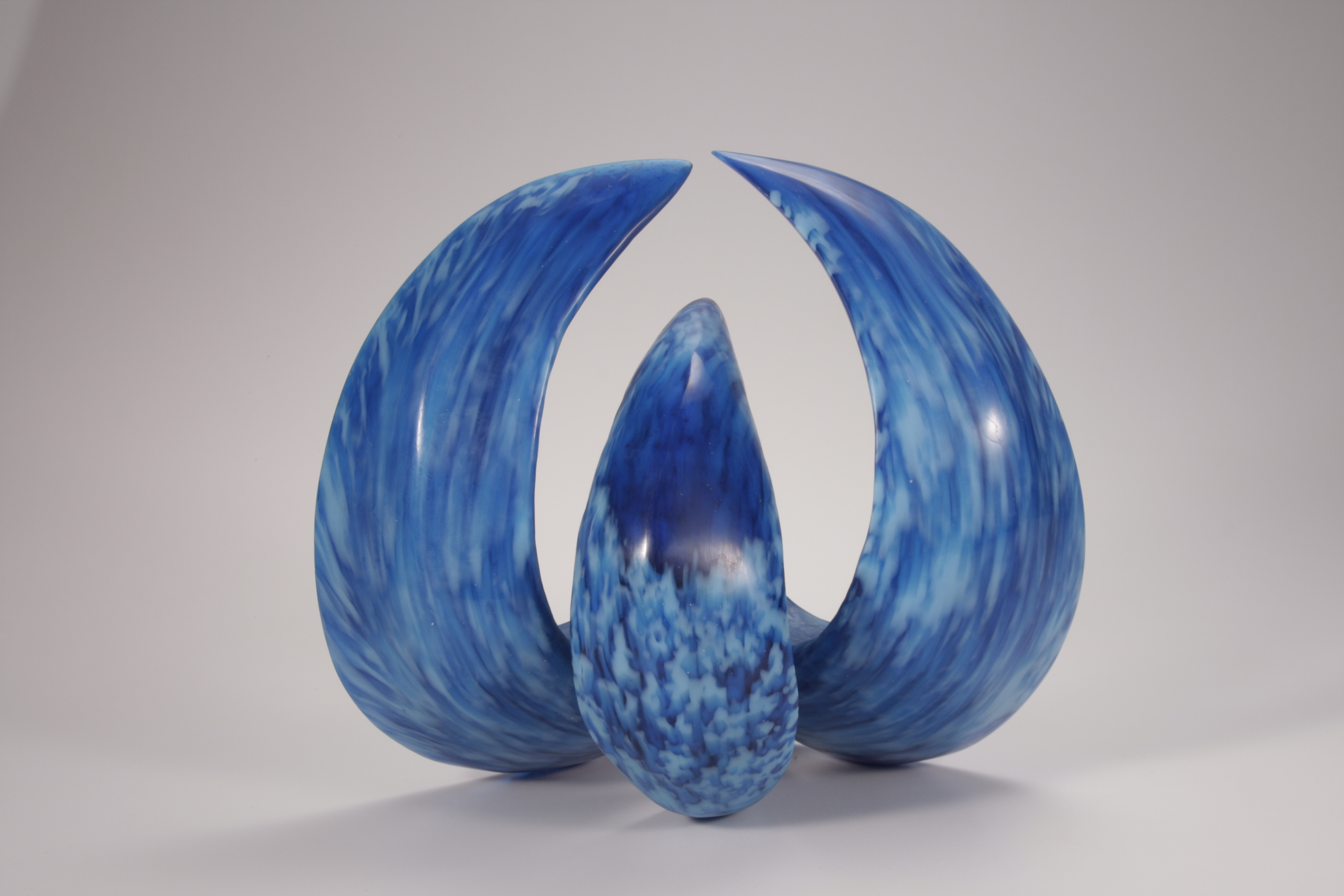 Sculpture of cast glass wave form in turquoise and light blue, back view.